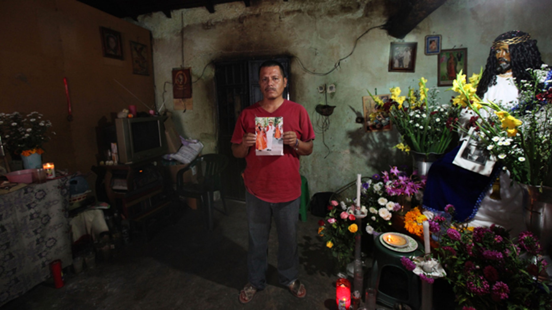Clemente Rodriguez holds a photo of his missing son Christian Rodriguez Telumbre in his home in Tixtla, Mexico.