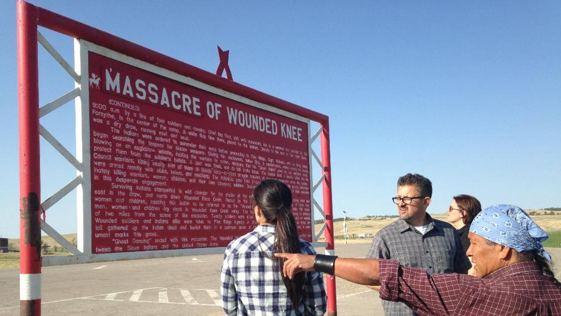 In this May 1, 2015 photo, Native American cartoonist Ricardo Cate', far right, and Chicano cartoonist Lalo Alcaraz, third right, visit Wounded Knee Memorial at Wounded Knee, S.D., on the Pine Ridge Indian Reservation. The nightclub attack in Orlando was initially described by some news organizations, including The Associated Press, as the deadliest mass shooting in U.S. history. In truth, America has seen even bigger massacres, some involving hundreds of men, women and children, like the one at Wounded Knee in 1890 against the Lakota. (AP Photo/Russell Contreras)