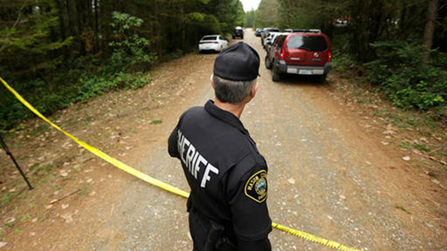 Mason County Sheriff's Chief Criminal Deputy Russ Osterhout looks down a road near the scene of a fatal shooting Friday, Feb. 26, 2016, near Belfair, Wash. (AP Photo/Ted S. Warren)