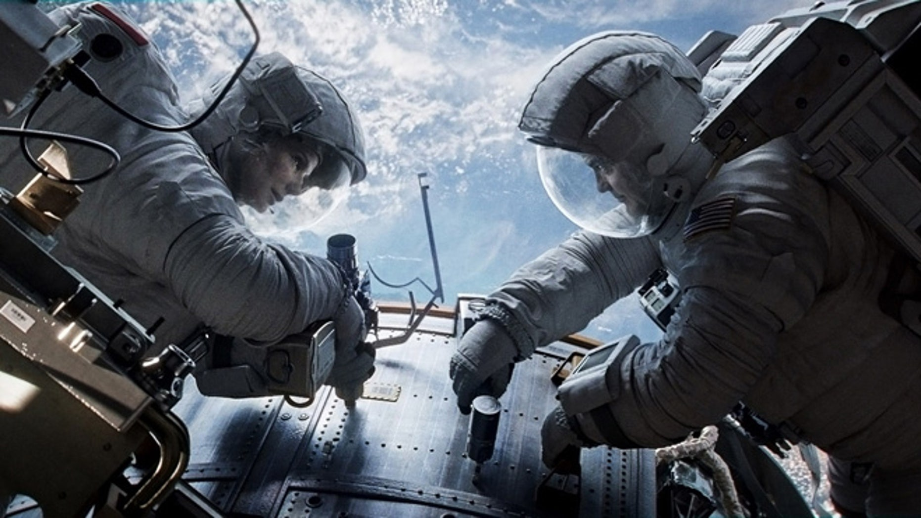 """This publicity photo released by Warner Bros. Pictures shows Sandra Bullock, left, as Dr. Ryan Stone and George Clooney as Matt Kowalsky in """"Gravity."""""""