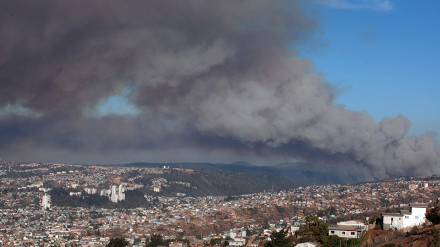 Plumes of smoke from a wild fire rise over Valparaiso, Chile, Friday, March 13, 2015. A serious forest fire spread quickly on Chile's coast Friday and threatened to reach the nearby port cities of Valparaiso and Vina del Mar. Deputy Interior Secretary Mahmud Aleuy said that thousands have been evacuated as flames advanced nearby. (AP Photo)