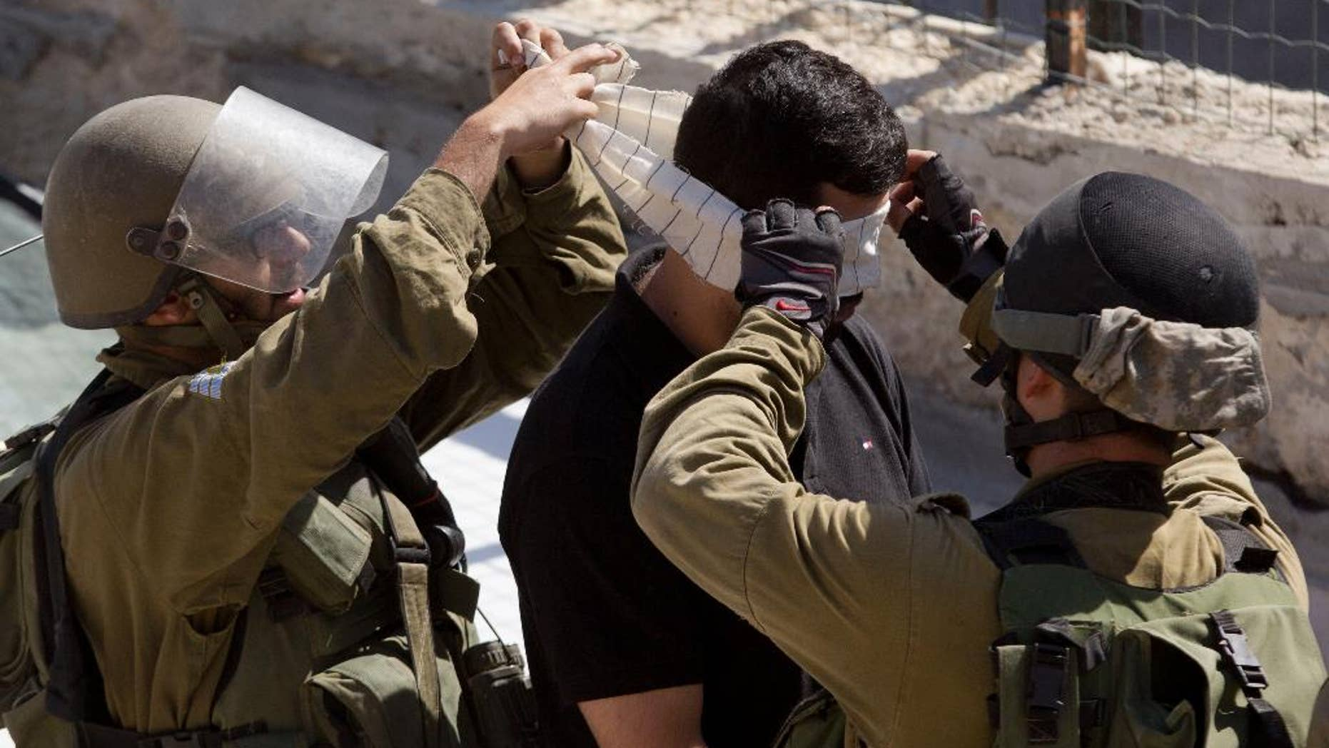 Israeli troops arrest a Palestinian during clashes after the funeral of Ibrahim Awad, 28, in the village of Beit Ummar near the West Bank city of Hebron, Thursday, Sunday, Oct. 11, 2015. Awad died of his wounds on Saturday after being shot by Israeli troops during a protest last week. (AP Photo/Majdi Mohammed)