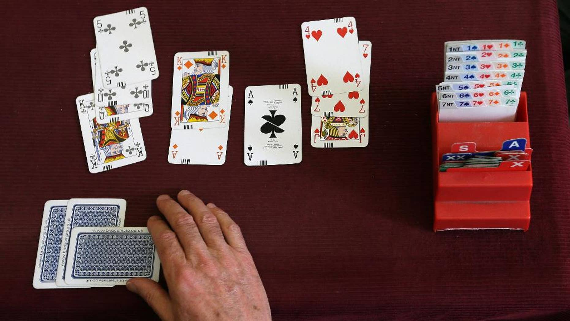 FILE - This is a Tuesday Sept. 22, 2015 file photo of  a competitor playing bridge at the Acol Bridge Club in West Hampstead, London. A High Court judge on Thursday Oct. 15, 2015  backed Sport England's assertion that bridge is not a sport because it does not involve physical activity. English Bridge Union officials had challenged the ruling in court. (AP Photo/Tim Ireland, File)