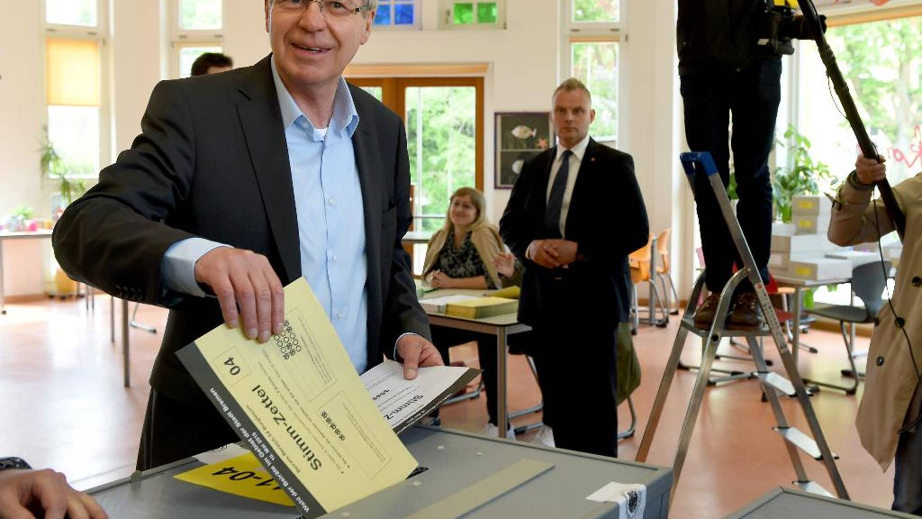 Mayor of Bremen Jens Boehrnsen casts his vote for the state election at a polling station in Bremen, Germany, Sunday, May 10, 2015. Germany's smallest state Bremen has been led by the center-left Social Democrats since the 1940s and polls point to a majority for popular Mayor Boehrnsen's current coalition with the Greens in the regional legislature. (Ingo Wagner/dpa via AP)