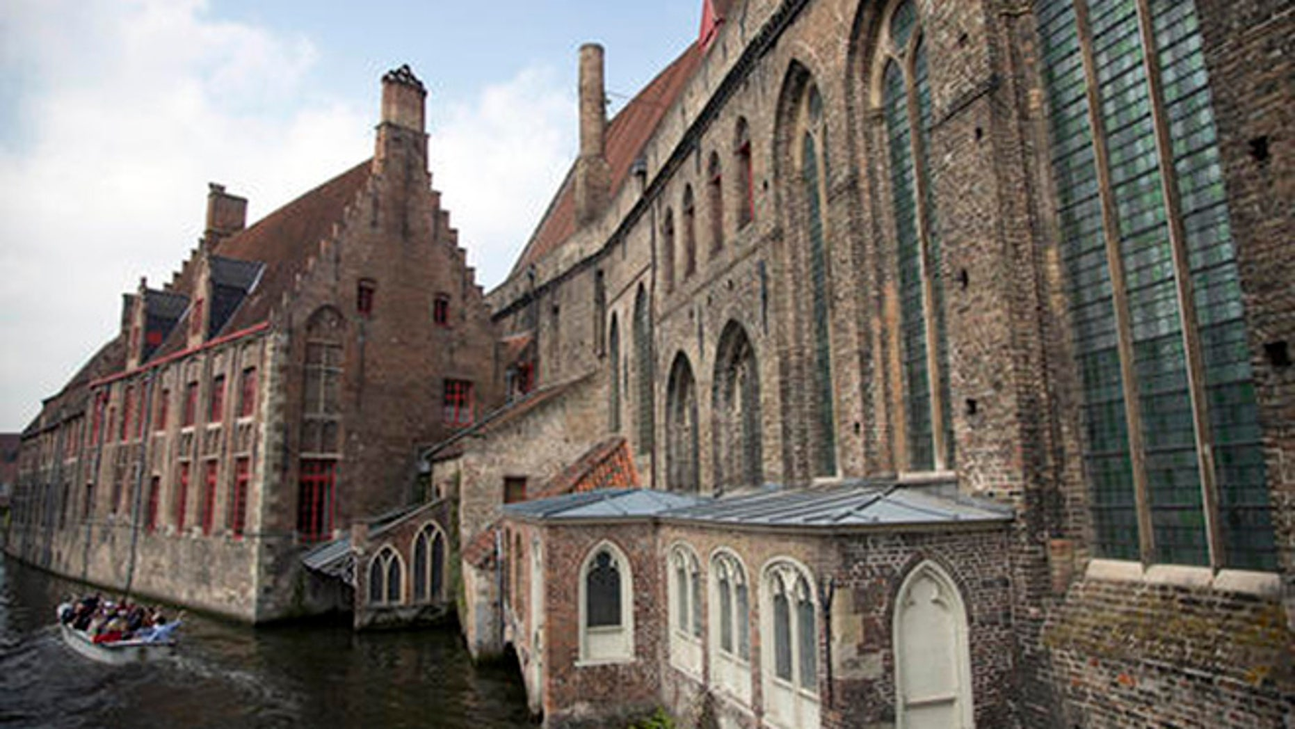 Tourists ride in a boat down a main canal past the Hospital St. Jan in Bruges, Belgium on Thursday, May 26, 2016.