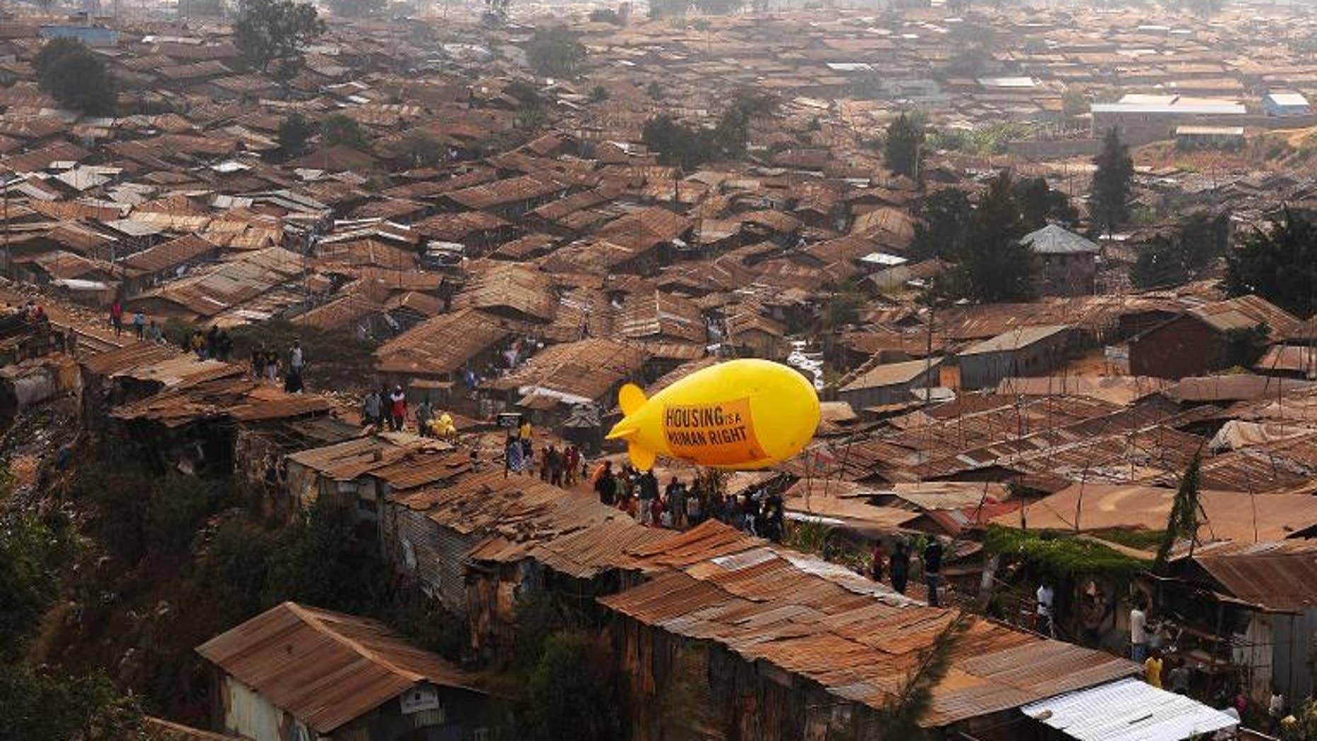Members of NGO Amnesty International carry a hot air balloon with text which reads 'Housing is a Human right' through the Kibera slum in Nairobi on March 24, 2012