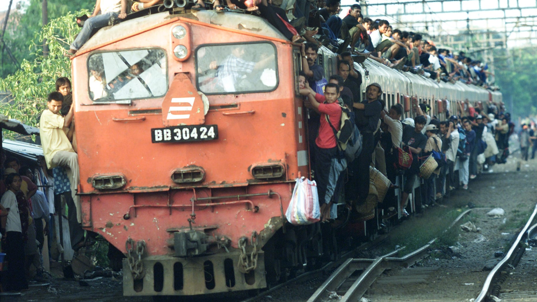 Nov. 12, 2004: Indonesian men hold on to the rooftop and outside of a train bound for Banten province. Indonesia has gone to imaginative extremes to try to stop commuters from riding the roofs of trains by suspending rows of grapefruit-sized concrete balls above railway lines a few inches above the tops of carriages at points where trains enter or pull out of stations, or where they go through crossings.
