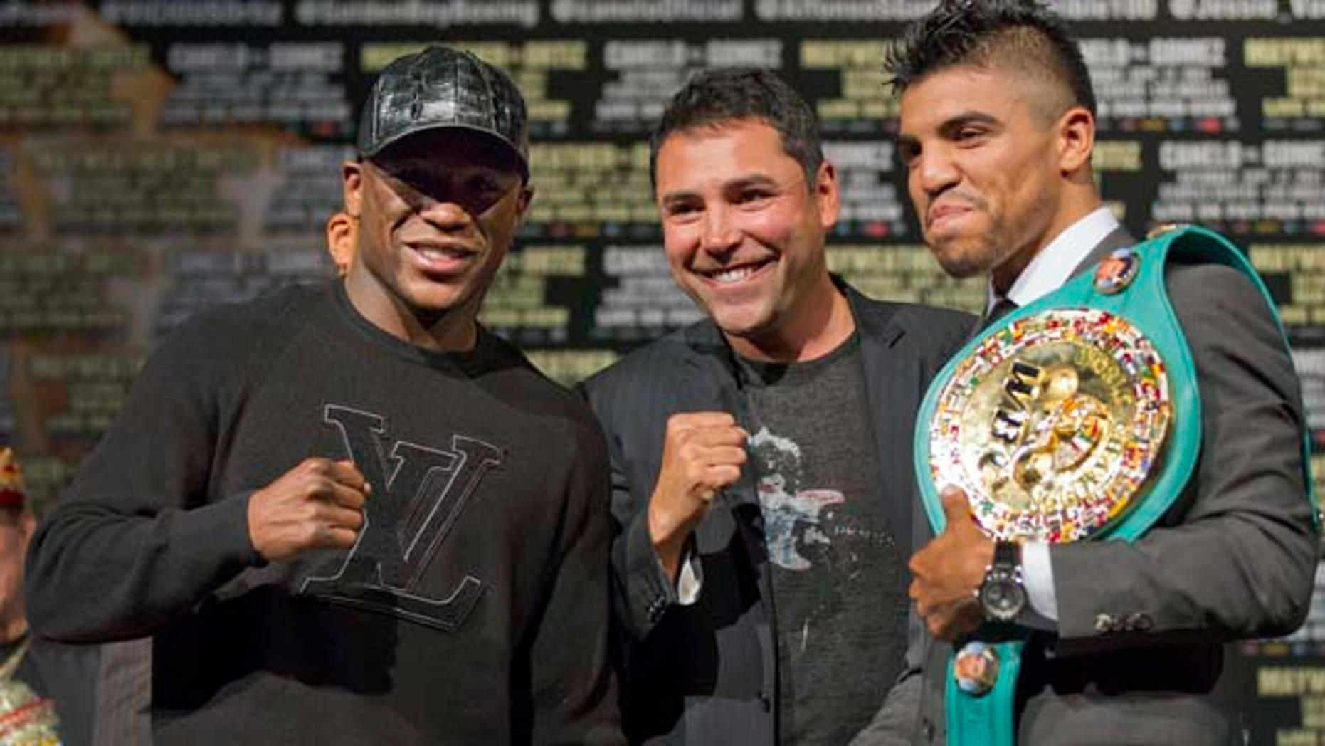 September 14, 2011: Floyd Mayweather, left, and Victor Ortiz, right, pose for a photo with Oscar De La Hoya after a news conference.