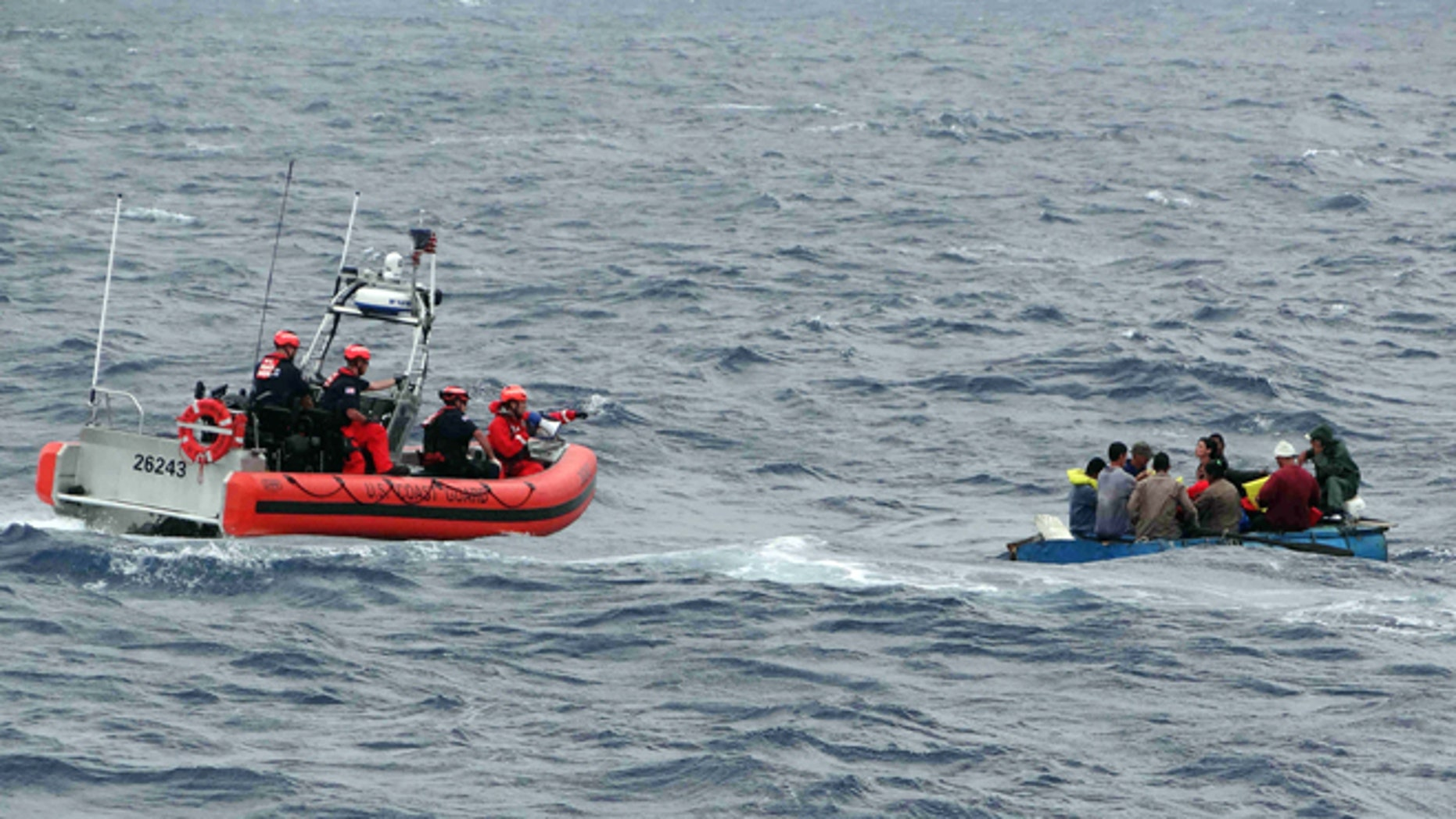 Coast Guard personnel left, try to assist a group of Cuban migrants on a makeshift vessel in the Florida Straits.