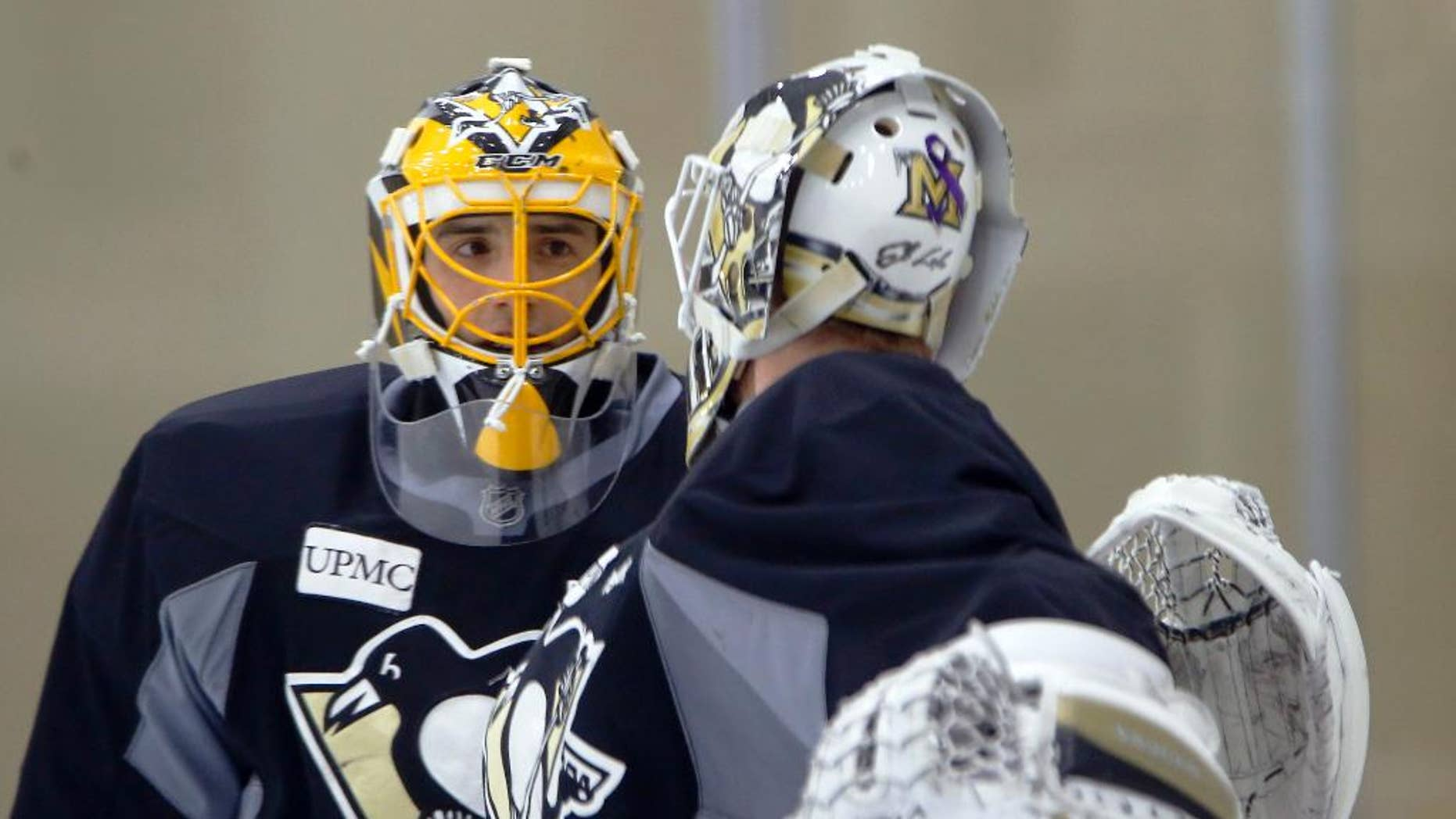 Pittsburgh Penguins goalie Marc-Andre Fleury, who has been out of action with concussion symptoms, talks with goalie Jeff Zatkoff during a practice session for the NHL hockey playoffs against the New York Rangers, Monday, April 11, 2016, at their practice facility in Cranberry, Pa. (AP Photo/Keith Srakocic)