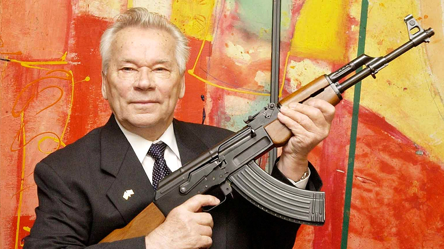 """July 26, 2002 - FILE photo of Russian weapon designer Mikhail Kalashnikov presenting his legendary assault rifle to the media while opening the exhibition """"Kalashnikov - legend and curse of a weapon"""" at a weapons museum in Suhl, Germany. Kalashnikov died at the age of 94."""