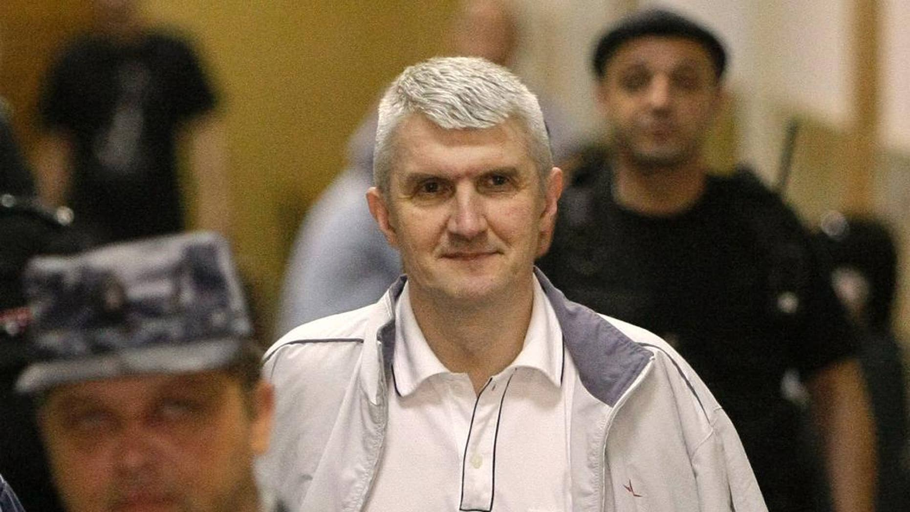 FILE - In this June 3, 2011 file photo, former Yukos CEO Mikhail Khodorkovsky's co-defendant Platon Lebedev, surrounded by guards, walks to a courtroom in Moscow. The Russian state has won three court cases recently in France that had entangled rocket builders in Yukos' efforts to recover money it says the Kremlin unfairly appropriated. Four more rulings are expected Friday April 15, 2016 in Paris. (AP Photo/Misha Japaridze, file)