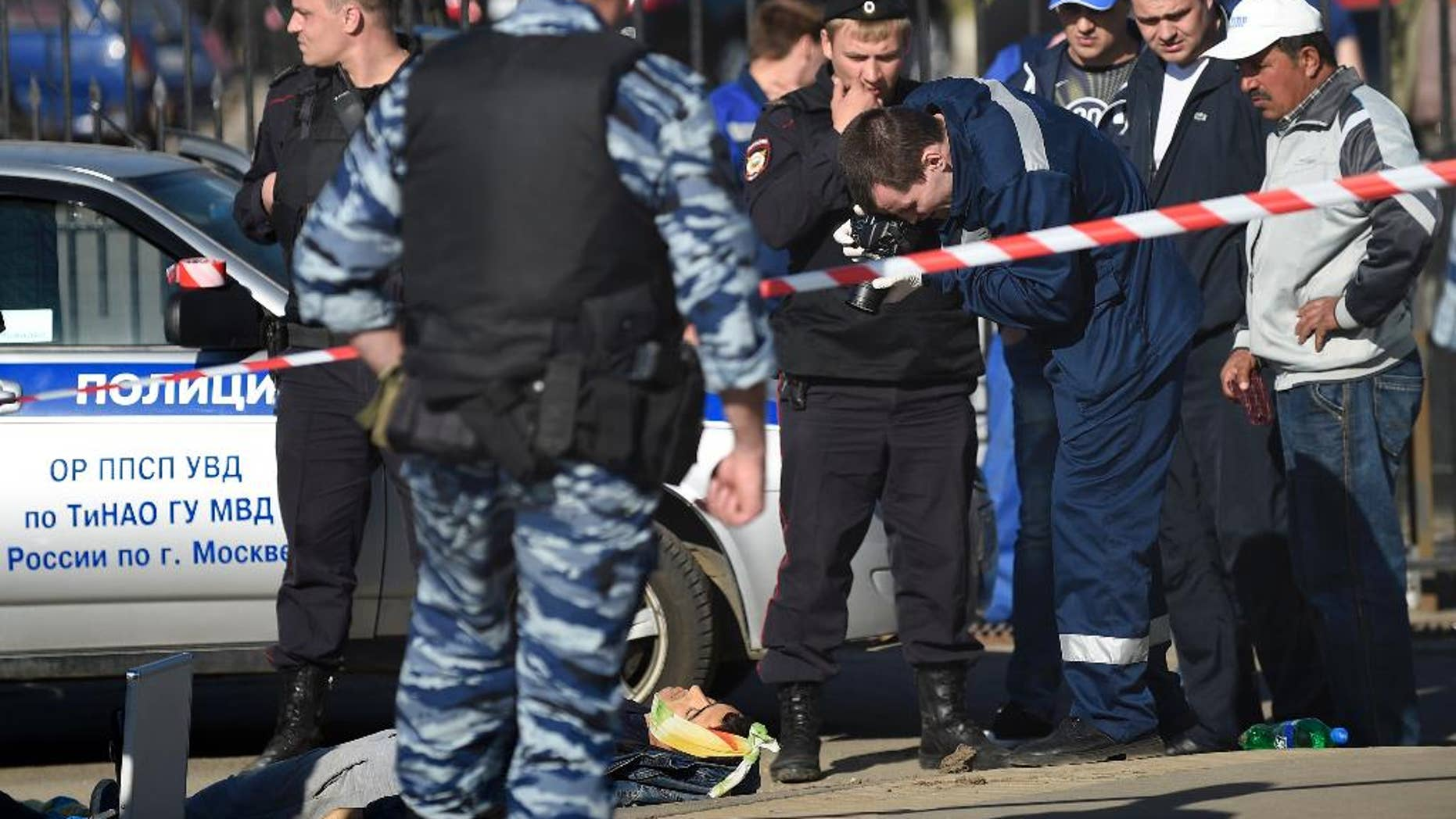 Police investigators work on the site of a brawl at the Khovanskoye cemetery in in Moscow, Russia, Saturday, May 14, 2016. Moscow police say a brawl at a cemetery involving up to 200 people has left two people dead and 10 wounded. Russian news reports cited police as saying the brawl was believed to have been about control over providing burial services at the sprawling Khovanskoye cemetery in southwest Moscow. (AP Photo)