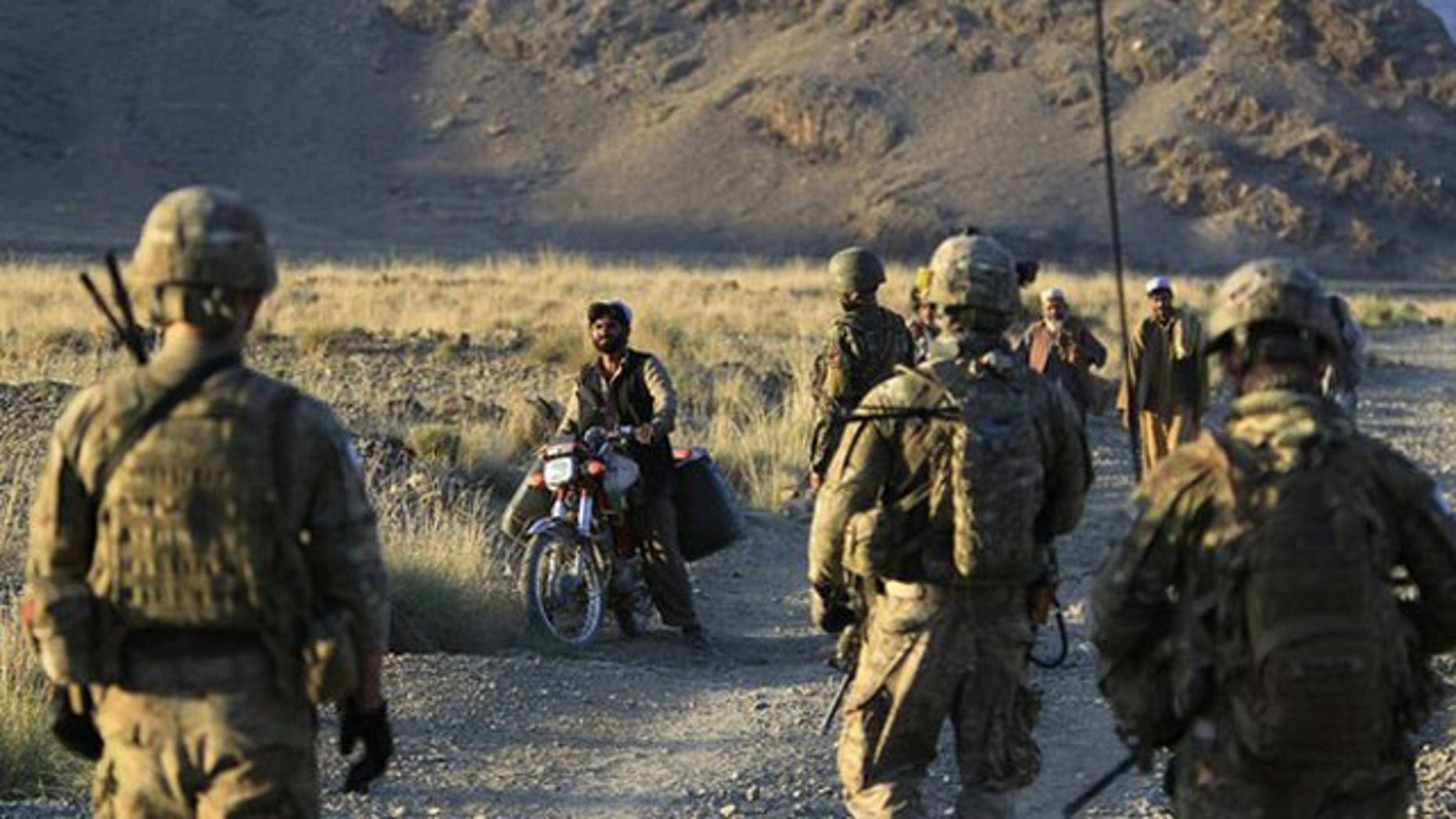 "October 2: U.S. soldiers from Alpha Co, 2nd Battalion 35th Infantry, Task Force ""Cacti"" and Afghan soldiers check villagers along a road during a joint military patrol in Walay valley, near the Afghanistan-Pakistanborder in Kunar province."