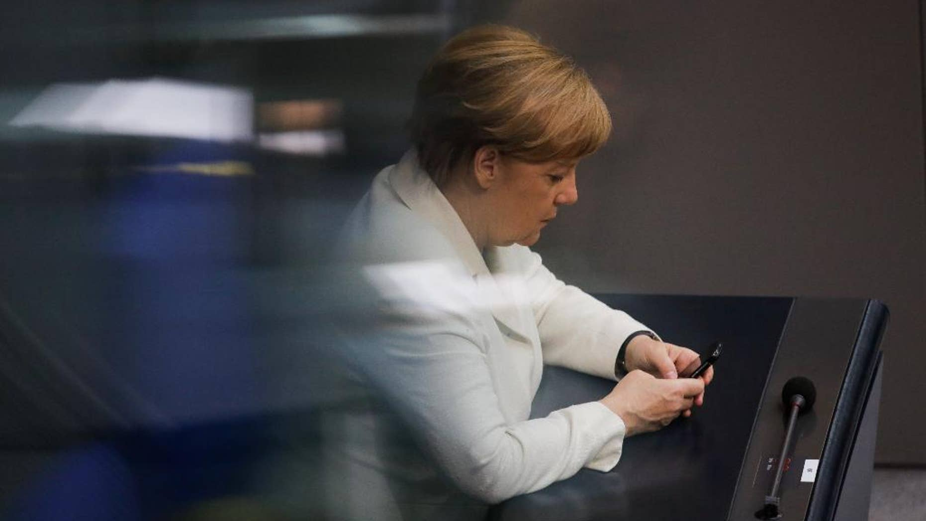 German Chancellor Angela Merkel uses her mobile devices as she attends a debate about a package of new measures to help fight terrorism at the German parliament Bundestag in Berlin, Thursday, June 9, 2016. (AP Photo/Markus Schreiber)