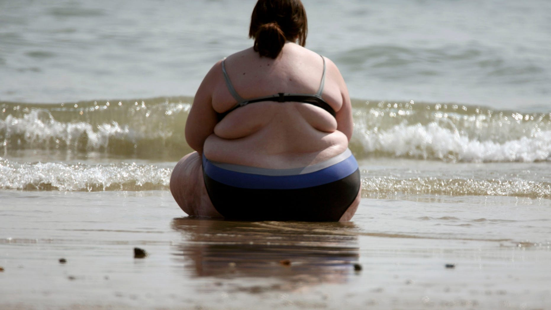 BOURNEMOUTH, UNITED KINGDOM - APRIL 14:  A woman sits at the water's edge as she enjoys the hot weather on the sea front on April 14 in Bournemouth, England. The un-seasonably warm weather has heralded the start to what weather forecasters predict will be a record breaking summer.  (Photo by Matt Cardy/Getty Images)