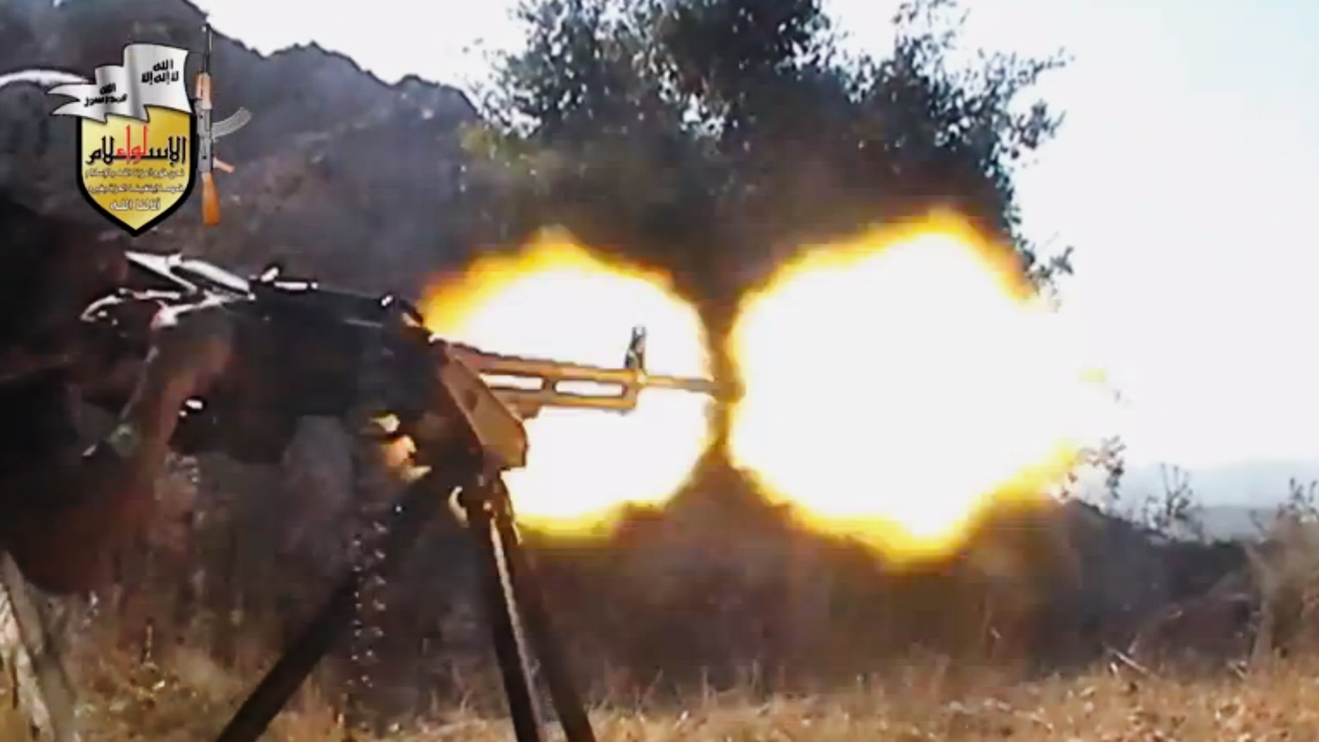 FILE - In this file image taken from Sunday, Aug. 11, 2013, video obtained from the Shaam News Network, which has been authenticated based on its contents and other AP reporting, a rebel fighter fires a gun in a valley in an unidentified location in Latakia province, Syria. Jihadi-led rebel fighters in Syria killed at least 190 civilians and abducted more than 200 during an offensive against pro-regime villages, committing a war crime, an international human rights group said Friday, Oct. 11, 2013. (AP Photo/Shaam News Network via AP Video, File)