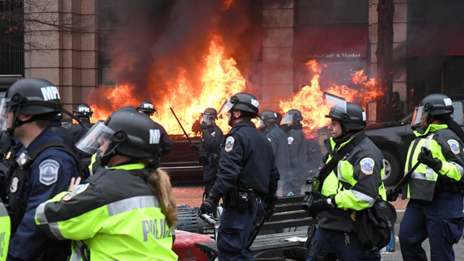 Police officers move protestors away from a car that was set on fire during protests near the inauguration of President Donald Trump in Washington, DC, U.S., January 20, 2017.  REUTERS/Bryan Woolston     TPX IMAGES OF THE DAY - RTSWL62