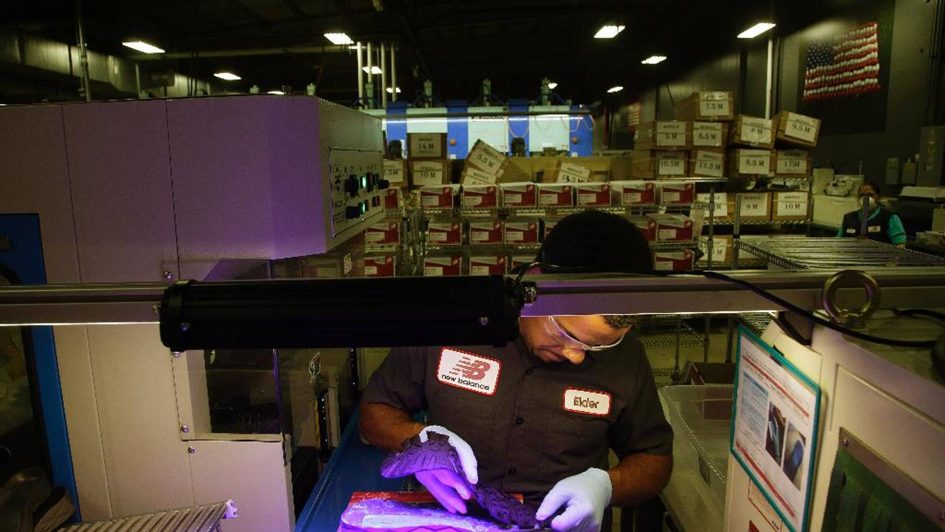 FILE - In this July 1, 2015 file photo, Elder Brandao, working under ultraviolet lights, glues an outsole to a midsole of the New Balance proposed 950v2 sneaker, that has passed military testing, at one of company's manufacturing facilities in Boston. The Institute for Supply Management, a trade group of purchasing managers, issues its index of manufacturing activity for August on Tuesday, Sept. 1, 2015. (AP Photo/Stephan Savoia, File)