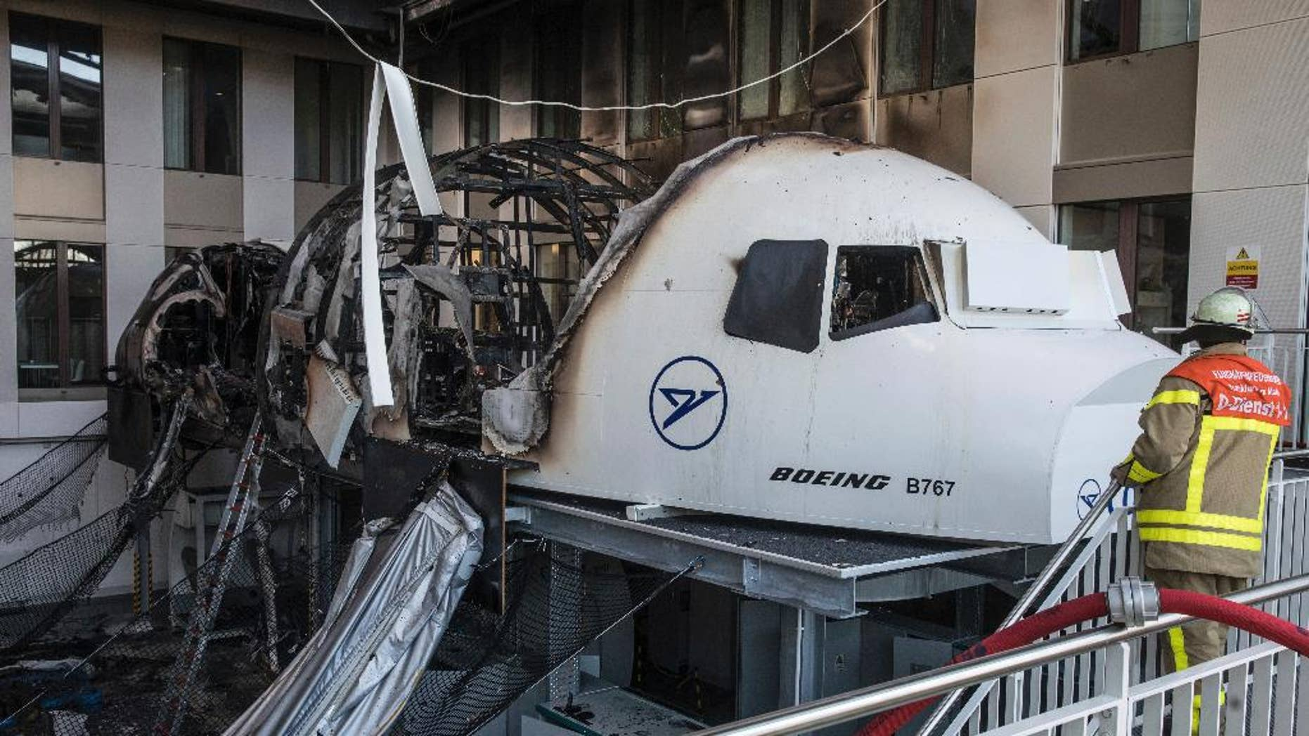 A firefighter stands in the office of Condor airlines next to a burned out flight simulator in the airport in Frankfurt am Main, Germany,  Thursday Dec. 29,  2016.  The flight simulator has caught fire in an office block at Frankfurt airport, forcing some 200 people to leave the building. The fire service says one person was taken to a hospital suffering from the effects of smoke inhalation.  (Frank Rumpenhorst/dpa via AP)