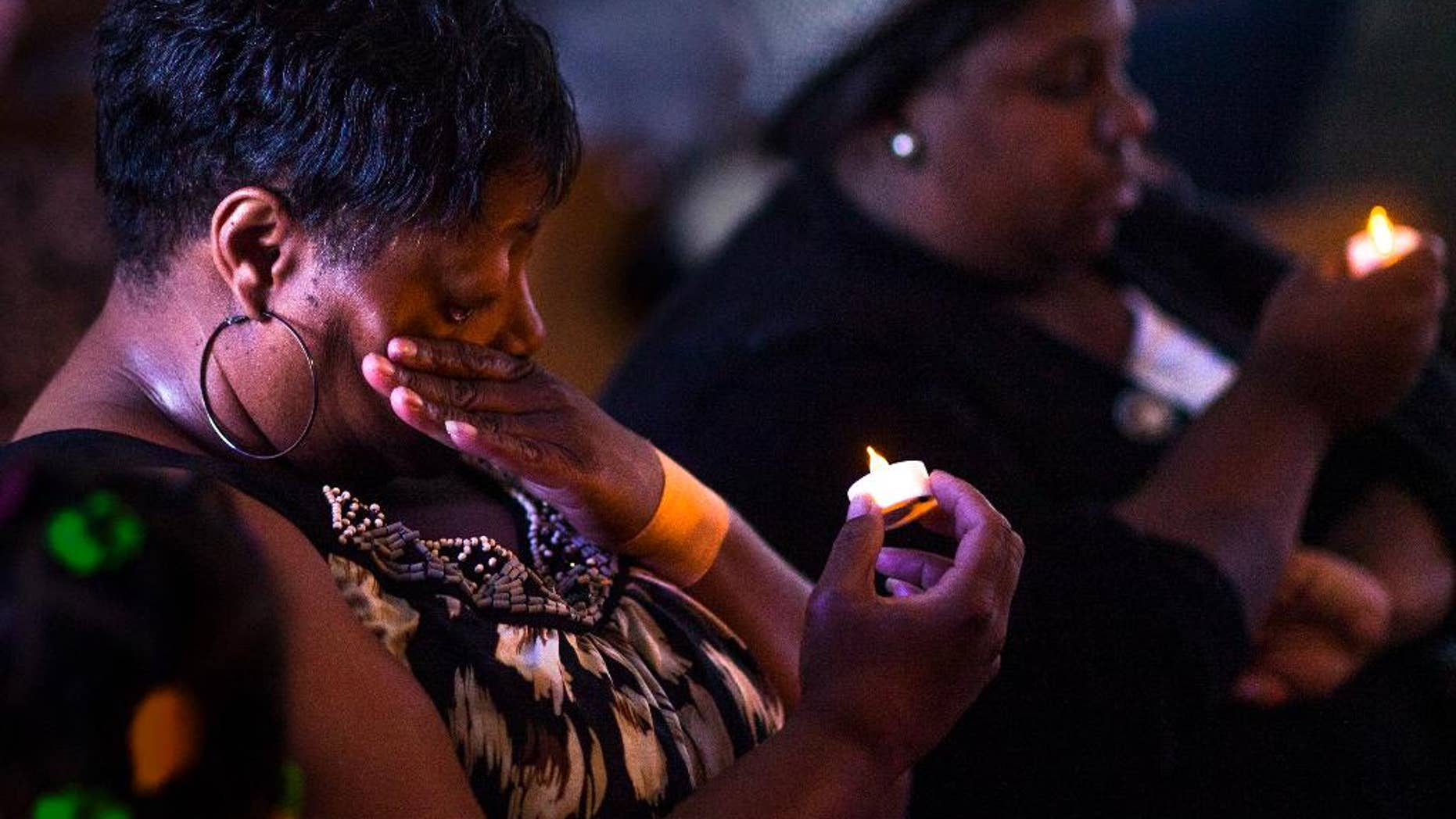Jackie Pillow wipes a tear from her eye during a vigil to mourn the lives lost at the shooting in Charleston, S.C., Thursday, June 18, 2015, at Taylor Chapel AME Church in Bowling Green, Ky. Dylann Storm Roof, 21, was arrested Thursday in the slayings of several people, including the pastor at a prayer meeting inside a historic black church. (Austin Anthony/Daily News via AP)