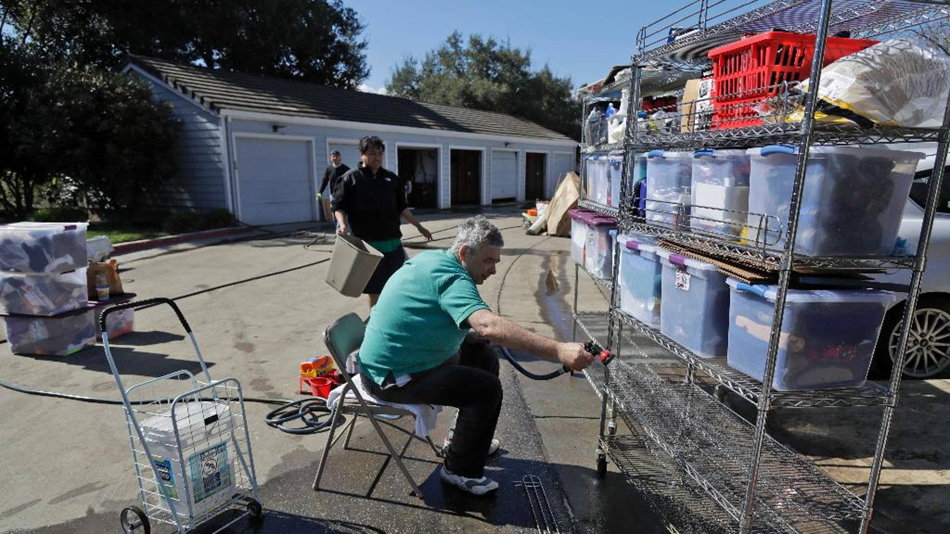 Residents wash their belongings as floodwaters recede along Coyote Creek Thursday, Feb. 23, 2017, in San Jose, Calif. Thousands of people evacuated from a flood in San Jose, California, returned home Thursday amid warnings to be careful about hygiene and handling food that may have come into contact with flood water. (AP Photo/Marcio Jose Sanchez)