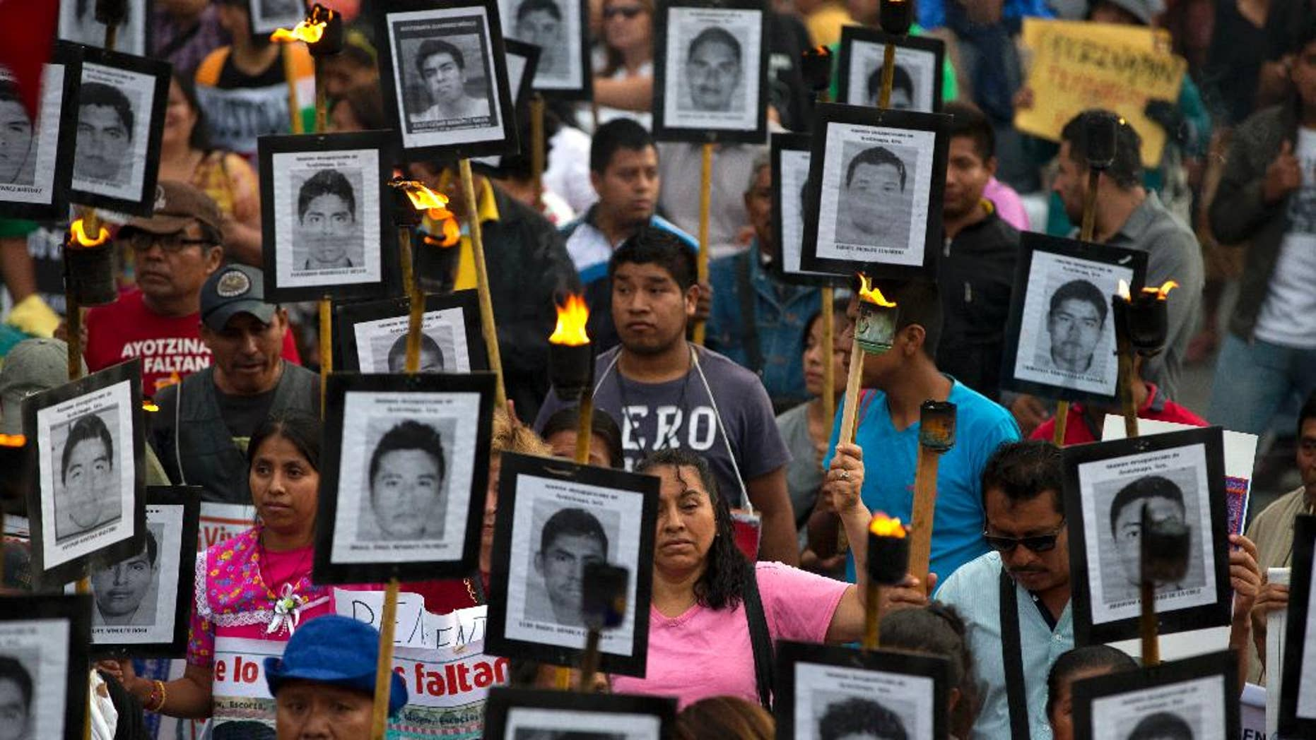 FILE - In this April 26, 2016 file photo, family members and supporters of 43 missing teachers college students carry pictures of the students as they march to demand the case not be closed and that experts' recommendations about new leads be followed, in Mexico City. The most recent forensic investigation of the southern Mexico garbage dump where the government says 43 students were incinerated did not confirm there was a fire there that night. It shows the experts found evidence the Cocula dump had been the site of at least five fires, but could not determine when. Remains of 17 people were also found, but it was unknown when they were burned. (AP Photo/Rebecca Blackwell, File)