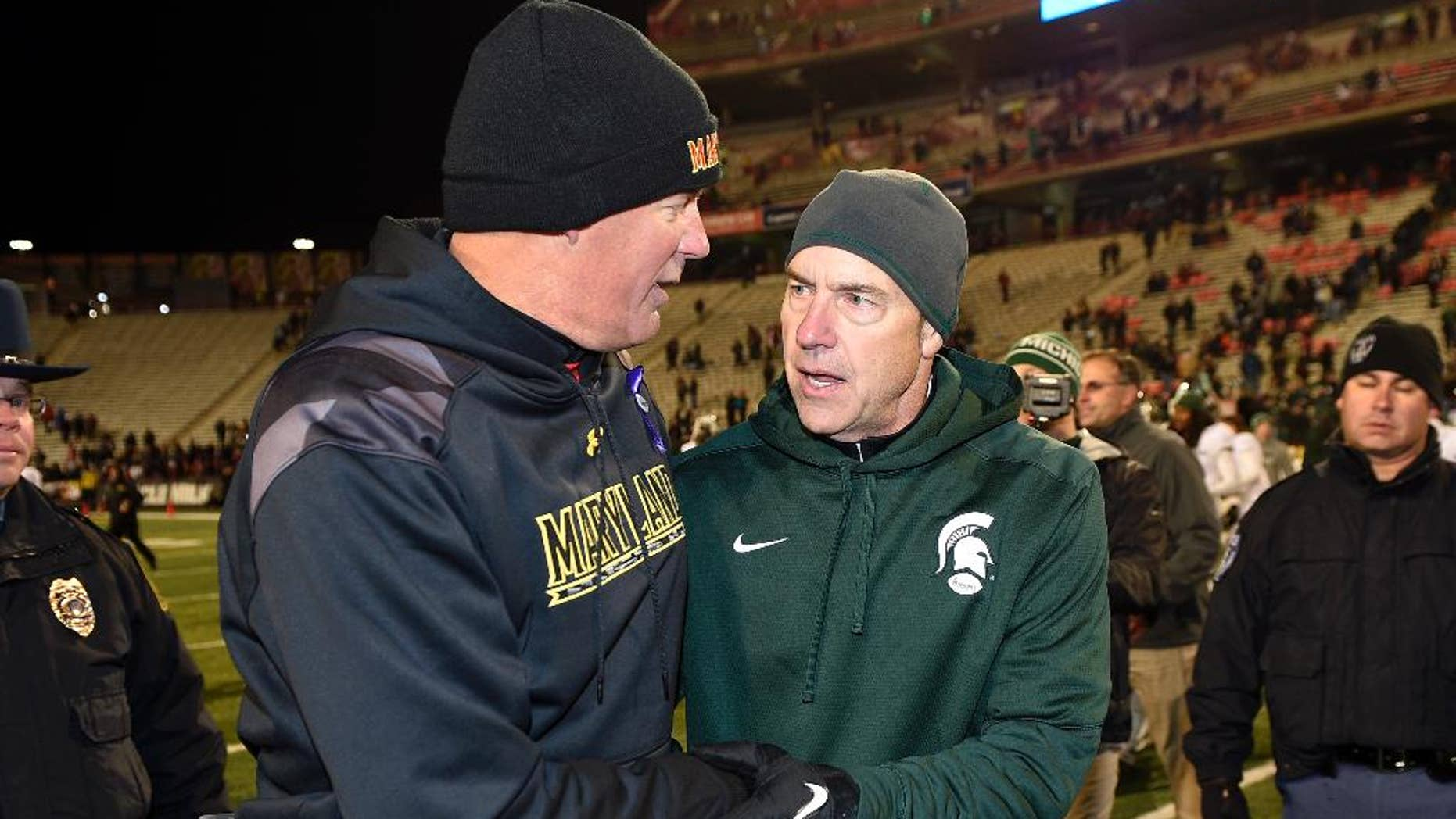 Michigan State coach Mark Dantonio, right, shakes hands with Maryland coach Randy Edsall, left, after an NCAA college football game, Saturday, Nov. 15, 2014, in College Park, Md. Michigan State won 37-15. (AP Photo/Nick Wass)