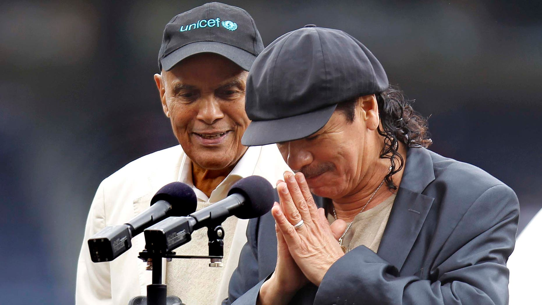 Musician Carlos Santana bows his head after receiving the Major League Baseball Beacon Award as Harry Belafonte. left, looks on during a pregame ceremony before the Atlanta Braves game against the Philadelphia Phillies in Atlanta, Sunday, May 15, 2011. (AP Photo/John Bazemore)