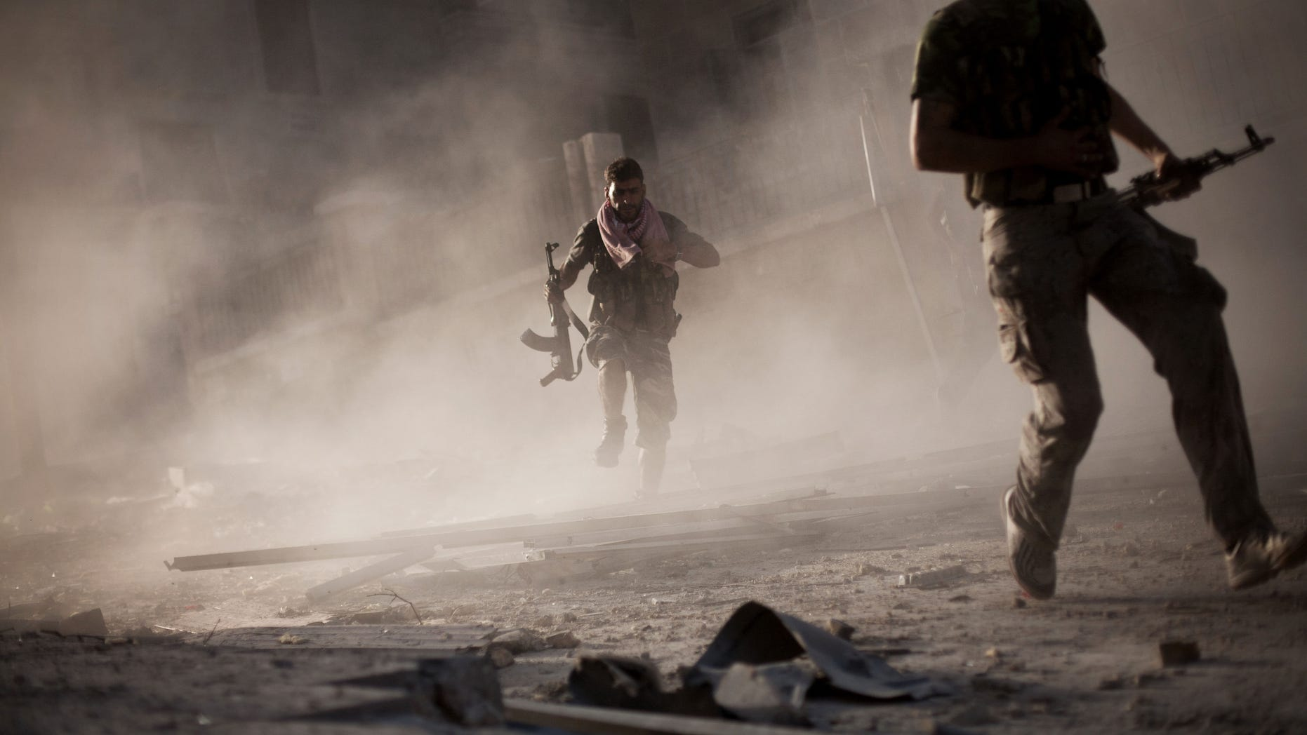 Sept. 7, 2012: In this photo, Free Syrian Army fighters run after attacking a Syrian Army tank during fighting in the Izaa district in Aleppo, Syria.