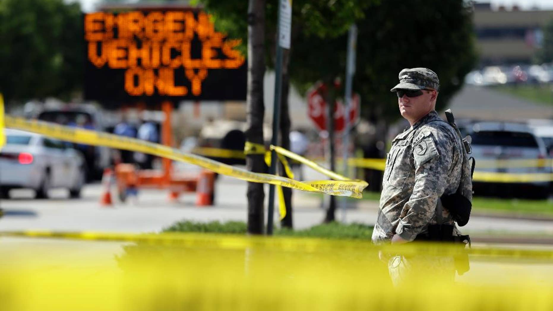 """A member of the Missouri National Guard stands guard at a police command post Tuesday, Aug. 19, 2014, in Ferguson, Mo. Ferguson's leaders urged residents Tuesday to stay home after dark to """"allow peace to settle in"""" and pledged several actions to reconnect with the predominantly black community in the St. Louis suburb where the fatal shooting of 18-year-old Michael Brown has sparked nightly clashes between protesters and police. (AP Photo/Jeff Roberson)"""
