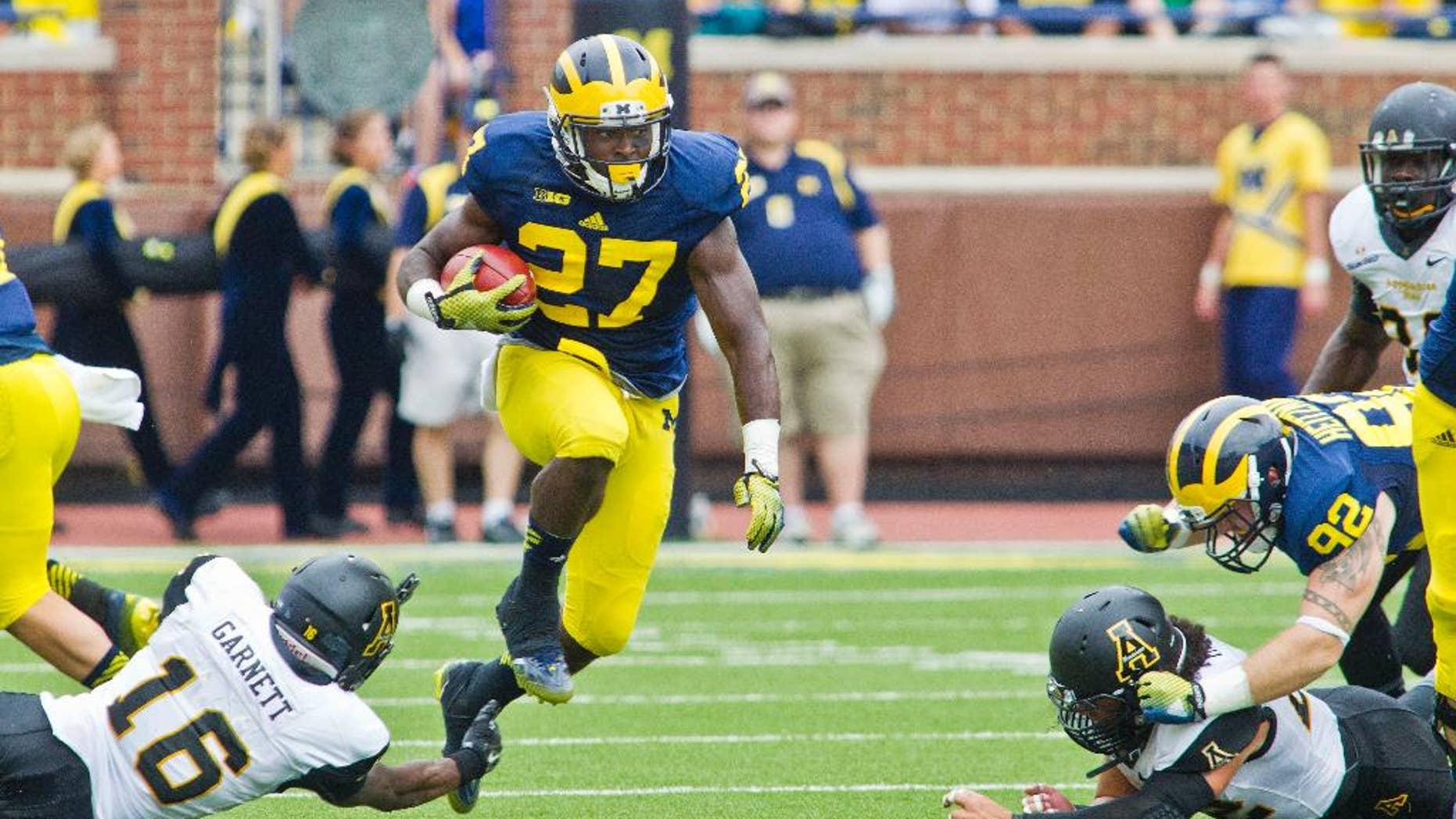 Appalachian State defensive back Treyon Garnett (16) fails to stop Michigan running back Derrick Green (27) in the third quarter of an NCAA college football game in Ann Arbor, Mich., Saturday, Aug. 30, 2014. Michigan won 52-14. (AP Photo/Tony Ding)