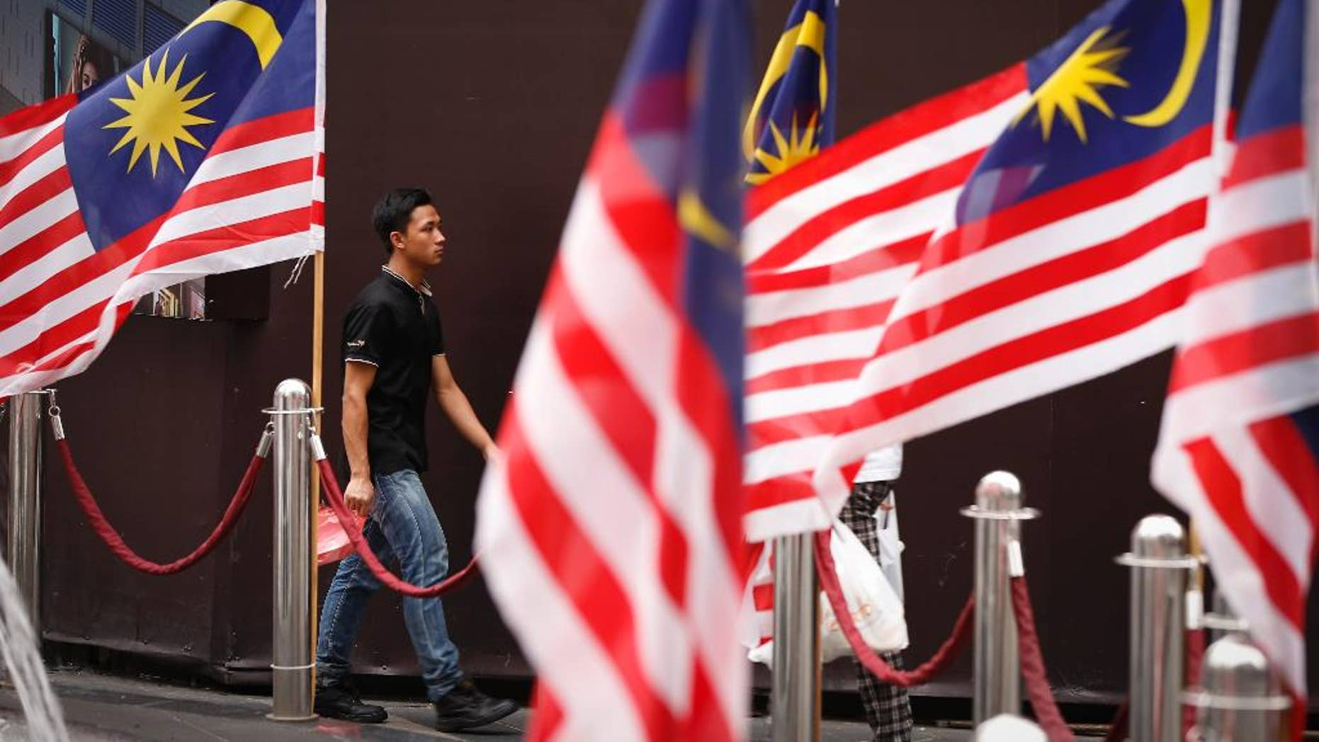 A man walks by displays of Malaysian national flags outside a shopping mall in Kuala Lumpur, Malaysia Wednesday, Aug. 12, 2015. A Malaysian opposition party Wednesday filed a civil lawsuit against Prime Minister Najib Razak for alleged election offenses involving $700 million in his bank accounts. (AP Photo/Vincent Thian)