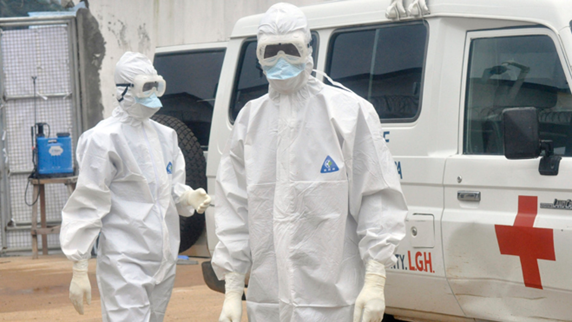 Health workers wearing protective gear wait to carry the body of a person suspected to have died from Ebola, in Monrovia, Liberia, Monday Oct. 13, 2014. Some nurses in Liberia defied calls for a strike on Monday and turned up for work at hospitals amid the worst Ebola outbreak in history. In view of the danger of their work, members of the National Health Workers Association are demanding higher monthly hazard pay. The association has more than 10,000 members, though the health ministry says only about 1,000 of those are employed at sites receiving Ebola patients. (AP Photo/Abbas Dulleh)
