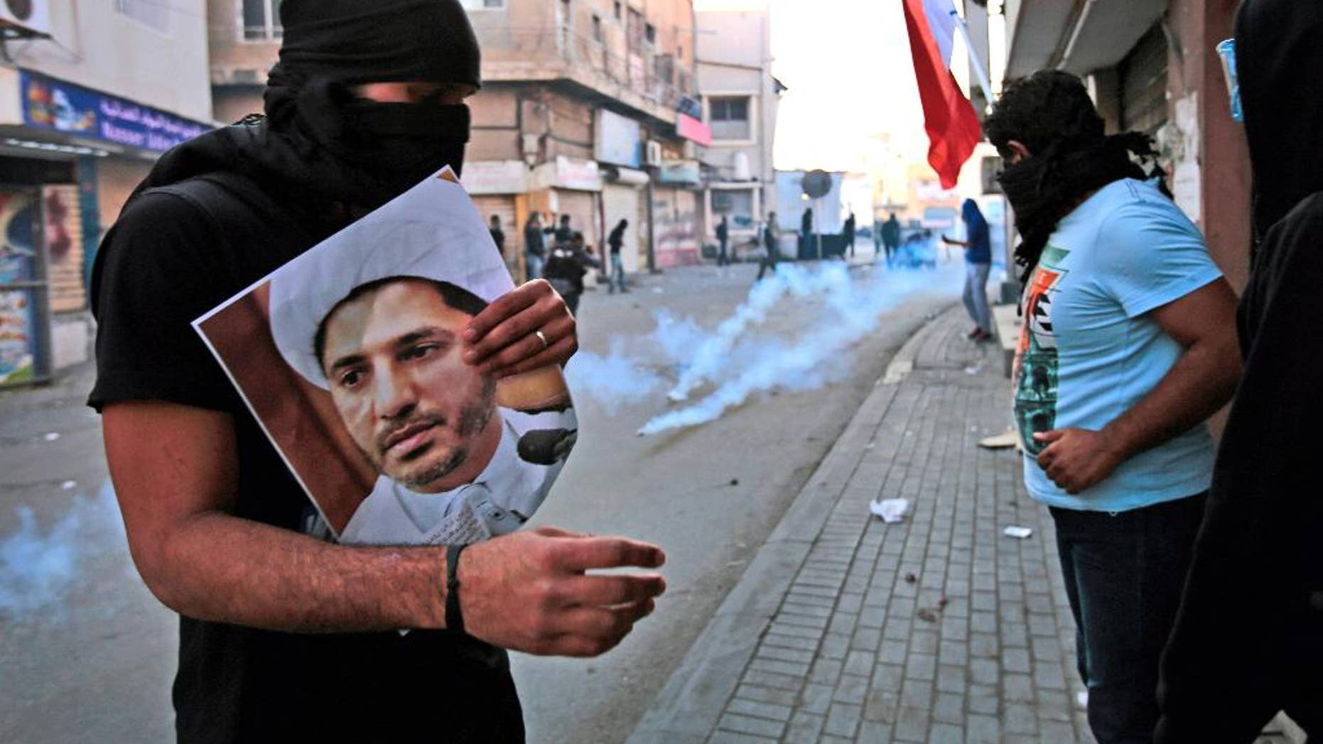 """FILE- In this Jan. 3, 2015 file photo, a masked Bahraini anti-government protester holds a picture of jailed Shiite cleric Sheik Ali Salman, the head of the opposition al-Wefaq political association, as riot police fire tear gas canisters during clashes in Bilad Al Qadeem, Bahrain. On Tuesday, June, 14, 2016, Bahrain said it has suspended all activities by Al-Wefaq, the largest Shiite opposition political group, and frozen its assets amid a widening crackdown on dissent, five years after the country's Arab Spring protests. A statement from the Justice and Islamic Affairs Ministry carried on the state-run Bahrain News Agency said a court made the decision to suspend Al-Wefaq to """"safeguard the security of the kingdom."""" (AP Photo/Hasan Jamali, File)"""