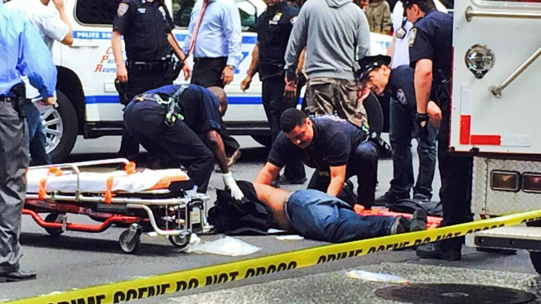 Medical technicians tend to David Baril, who was shot and wounded by police after he pulled a hammer from a bag and lunged at officers who approached him on the street near New York's Penn Station on Wednesday, May 13, 2015. Baril, 30, is suspected of attacking four people with a hammer earlier in the week. (AP Photo/Raj Mathura)