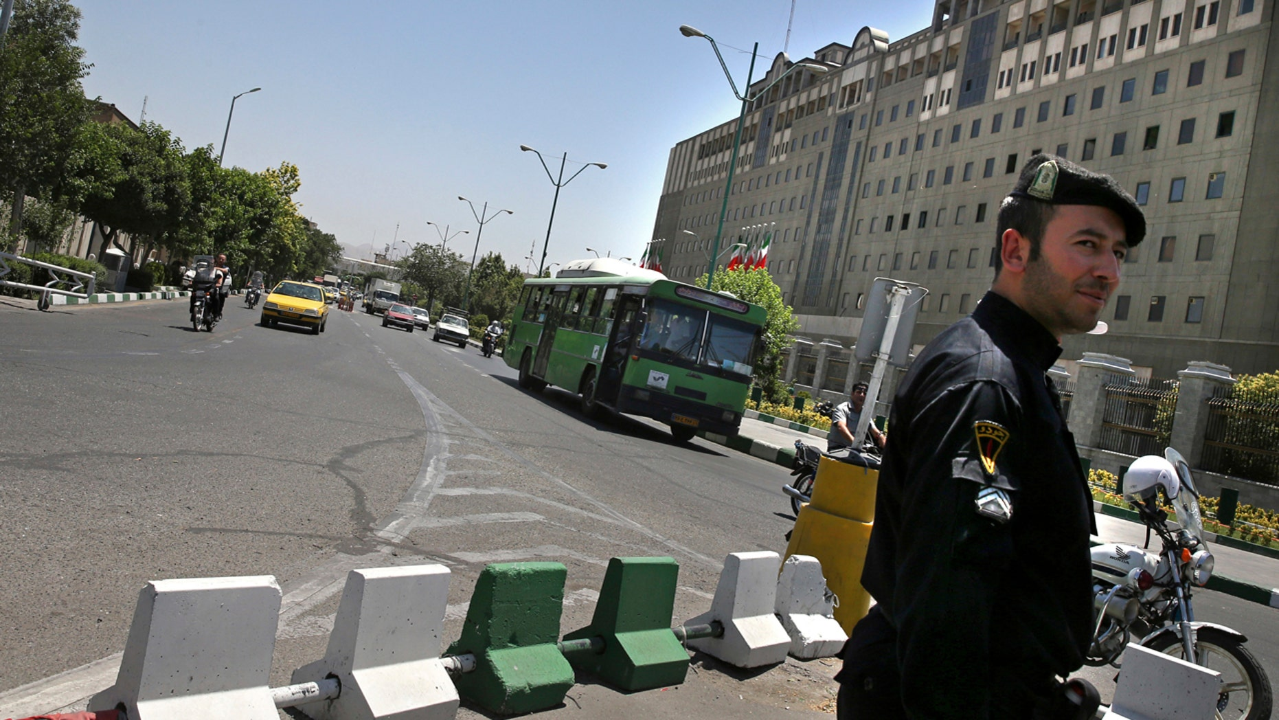 A police officer stands guard as vehicles drive in front of Iran's parliament building in Tehran, Iran, Thursday, May 8, 2017.