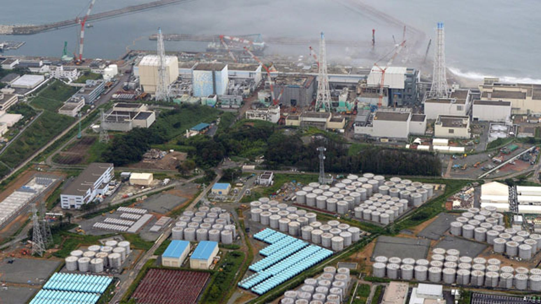 """FILE - This Aug. 20, 2013 aerial file photo shows the Fukushima Dai-ichi nuclear plant at Okuma in Fukushima prefecture, northern Japan. Japan's nuclear regulator has upgraded the rating of a leak of radiation-contaminated water at its tsunami-wrecked nuclear plant to a """"serious incident"""" on an international scale. (AP Photo/Kyodo News, File)"""