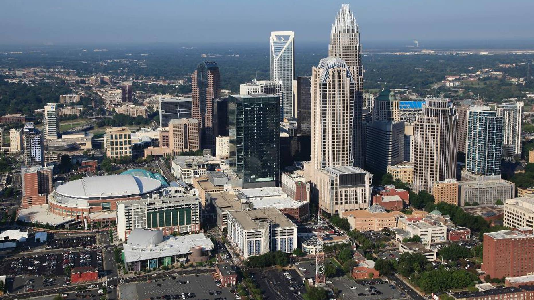 In this Aug. 16, 2012 file photo, the Time Warner Cable Arena is shown on left of downtown Charlotte, N.C.    To much of the world, Charlotte is the Queen City, a gleaming downtown, state-of-the-art stadiums, sparkling new mass transit, the nation's banking capital. But a very different Charlotte came into the spotlight in the past few days. Move outside the city's core and there are neighborhoods like the one where a police officer shot and killed a black man, Keith Scott, Sept. 20, 2016, setting off violent protests.(AP Photo/Chuck Burton)