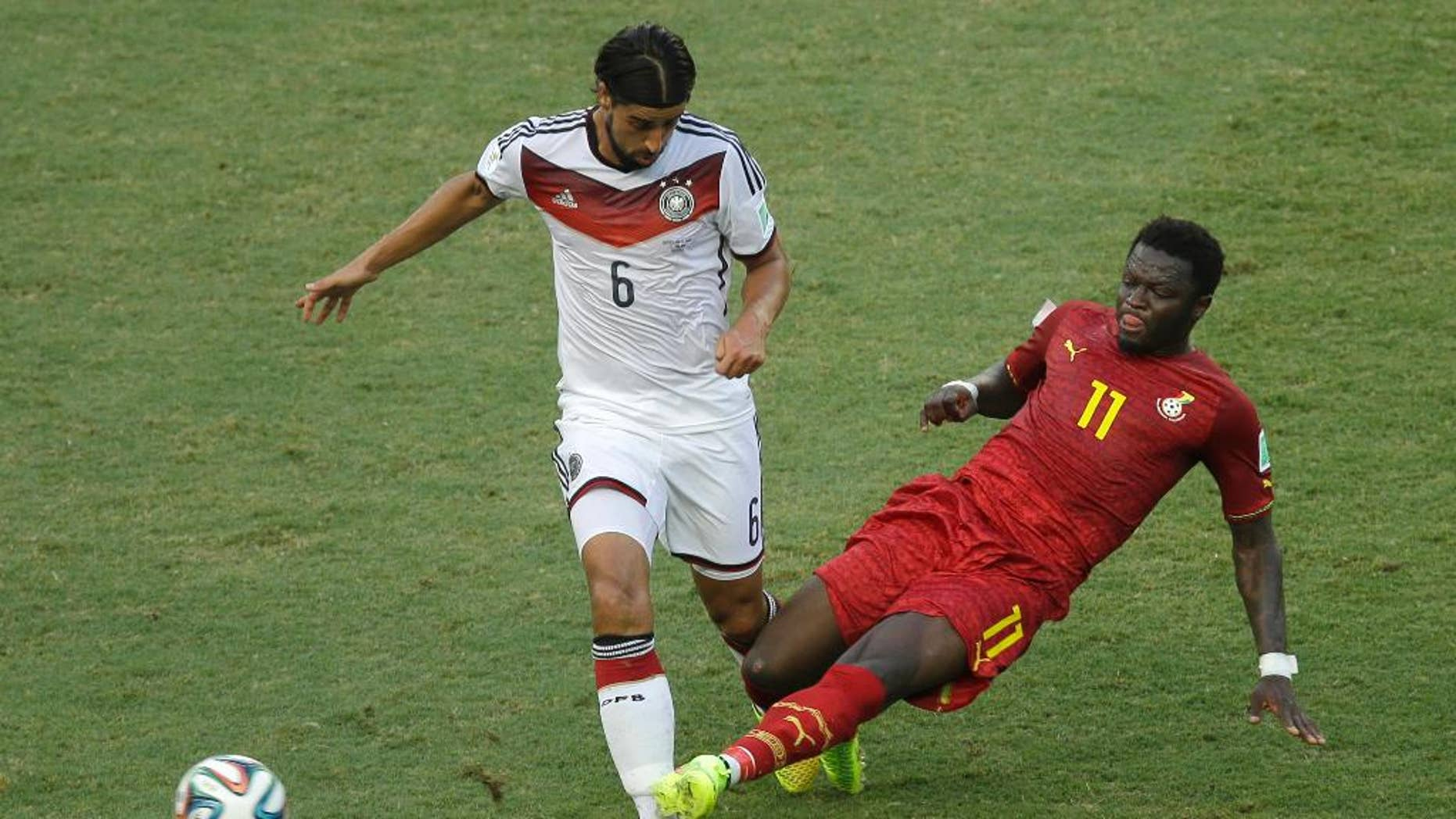 Germany's Sami Khedira, left, and Ghana's Sulley Muntari challenge for the ball during the group G World Cup soccer match between Germany and Ghana at the Arena Castelao in Fortaleza, Brazil, Saturday, June 21, 2014. (AP Photo/Themba Hadebe)