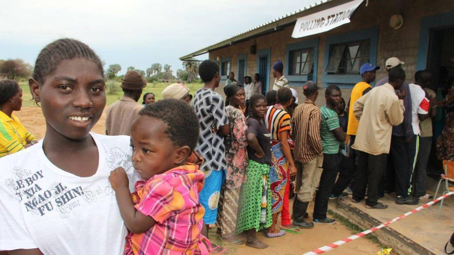 A voter carrying a child queues to cast her vote in the country's elections near Nkurenkuru, Namibia, Friday, Nov. 28, 2014. The southern African nation votes in parliamentary and presidential elections expected to deliver a comfortable win for the ruling party, which has been in power since independence in 1990. (AP Photo/Dirk Heinrich)