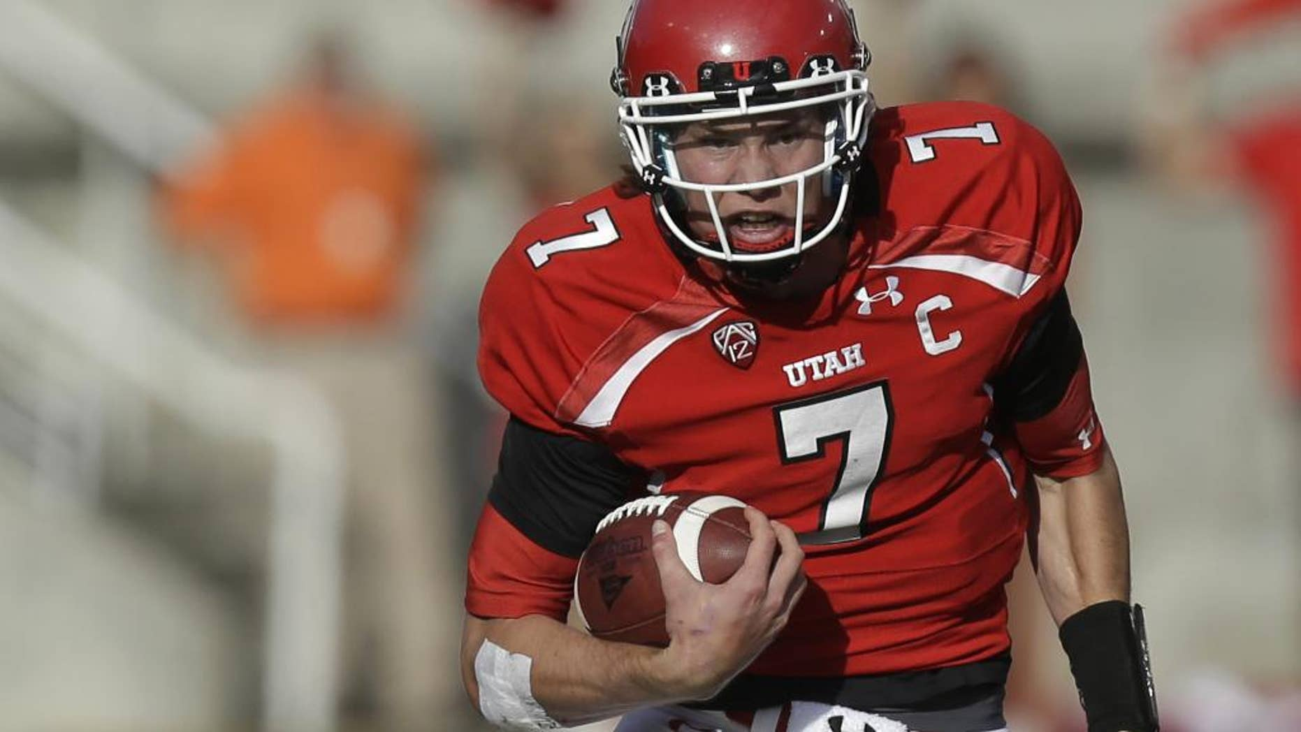 FILE - In this Nov. 9, 2013, file photo, Utah quarterback Travis Wilson carries the ball during an NCAA college football game against Arizona State in Salt Lake City. Wilson's first goal this season is to stay healthy.  (AP Photo/Rick Bowmer, File)