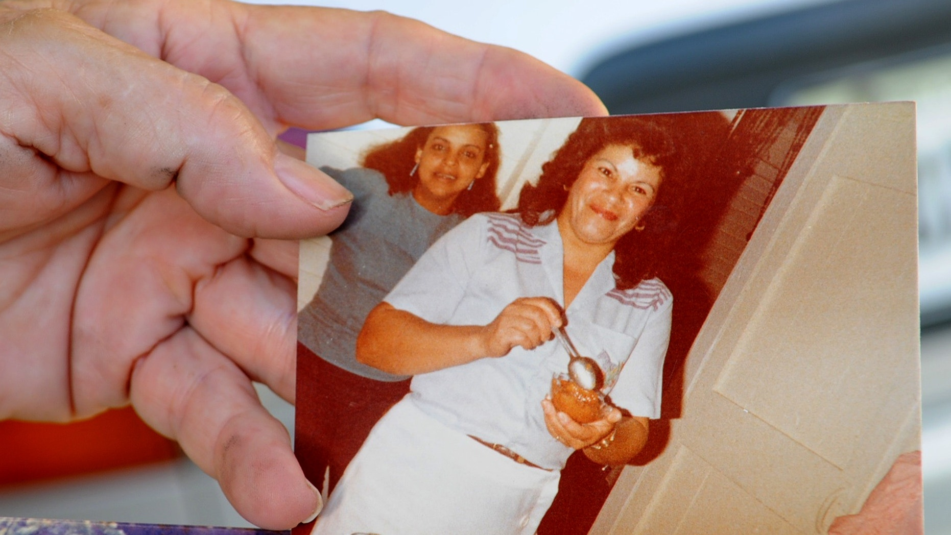 Miladys Ortega shows a photograph of her sister, Yoselyn Ortega, front center, taken some time between 1985 and 1990, at her home in Santiago, Dominican Republic, Saturday, Oct. 27, 2012.