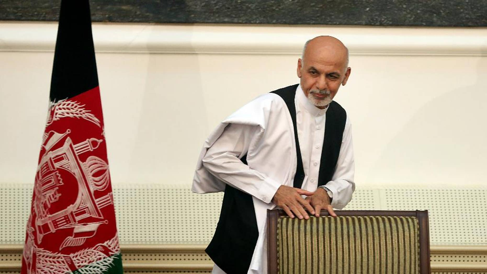 Afghanistan's presidential election candidate Ashraf Ghani Ahmadzai leaves after signing a power-sharing deal at the presidential palace in Kabul, Afghanistan, Sunday, Sept. 21, 2014. Ahmadzai, who will become president, and Abdullah Abdullah signed the national unity government deal as outgoing President Hamid Karzai watched.(AP Photo/Massoud Hossaini)