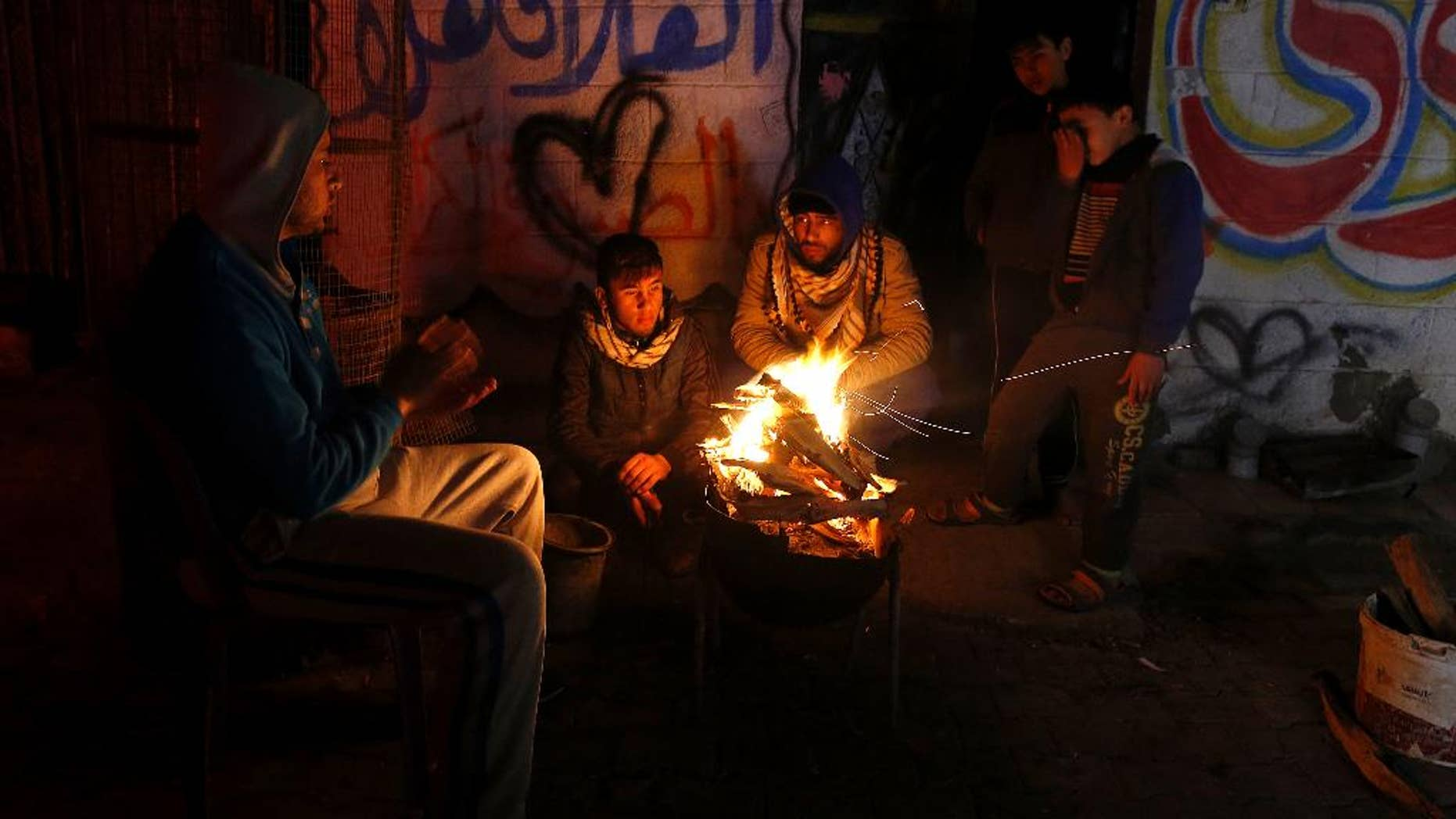 FILE -- In this Jan. 25, 2016 file photo, Palestinians, who get only several hours of electricity a day, sit around a fire outside their home in Gaza City. Israel said Thursday, April 27, 2017, that it was informed that the Palestinian self-rule government in the West Bank will stop paying for electricity Israel sells to the Gaza Strip. Abbas has threatened to exert financial pressure against political rival Hamas to cede control of Gaza, a territory it seized from him in 2007. Gazans now have electricity for only six hours a day. (AP Photo/Hatem Moussa, File)