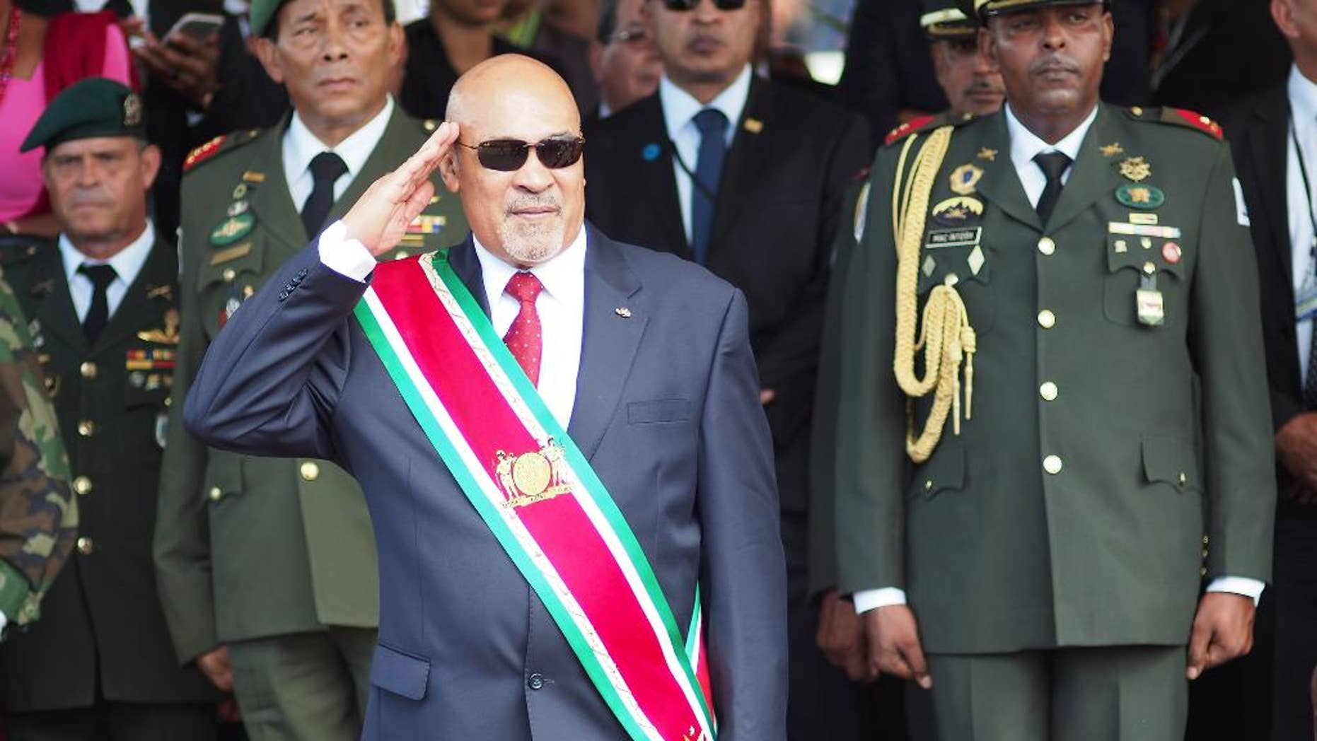 FILE - In this Aug. 12, 2015, file photo, Suriname President Desire Delano Bouterse salutes during a military parade, after being sworn in for his second term, in Paramaribo, Suriname. A two-time coup leader and former dictator accused of executing 15 political opponents in 1982, Bouterse has again moved on Wednesday, June 29, 2016, to prevent authorities in the South American nation from putting him on trial for those 15 deaths. (AP Photo/Ertugrul Kilic, File)