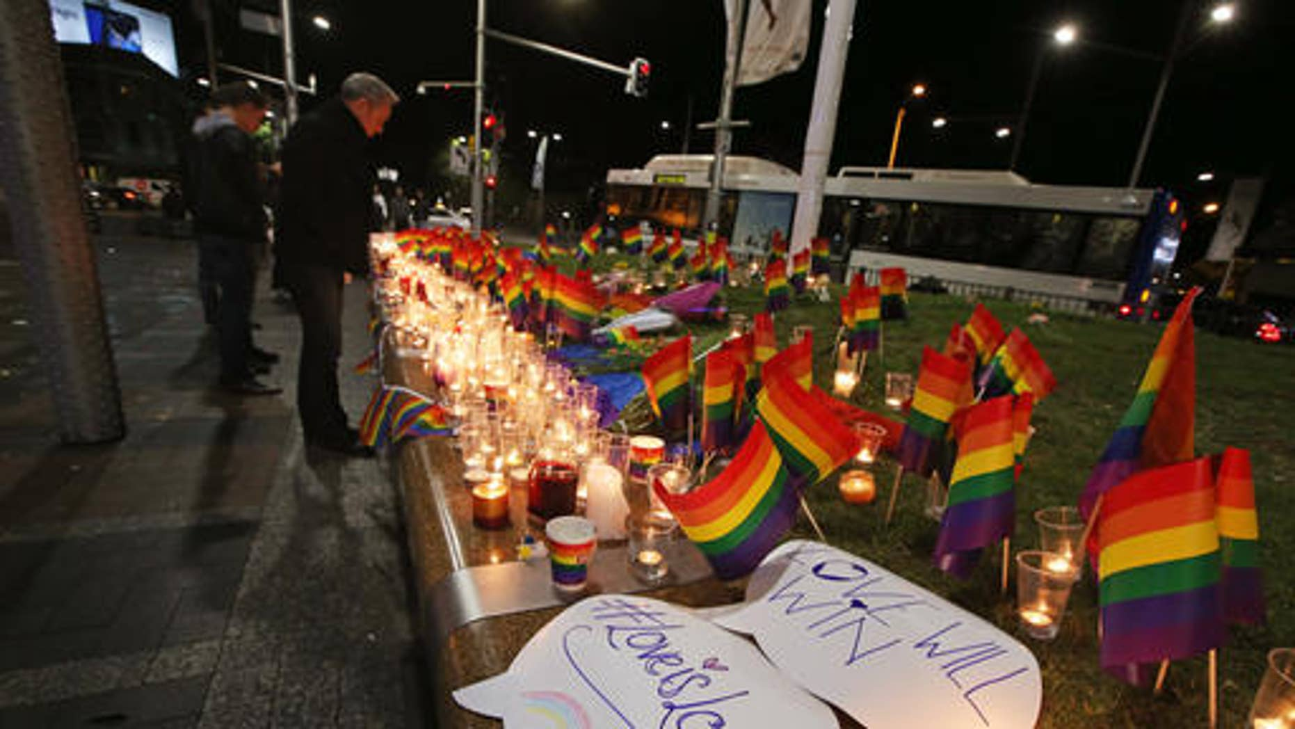 """An impromptu memorial is set up in Sydney, Monday, June 13, 2016, following the Florida mass shooting at the Pulse Orlando nightclub where police say a gunman wielding an assault-type rifle opened fire, killing at least 50 people and wounding dozens. Australian Prime Minister Malcolm Turnbull said that the Orlando mass shooting was """"an attack on all of us — on all our freedoms, the freedom to gather together, to celebrate, to share time with friends."""" (AP Photo/Rick Rycroft)"""