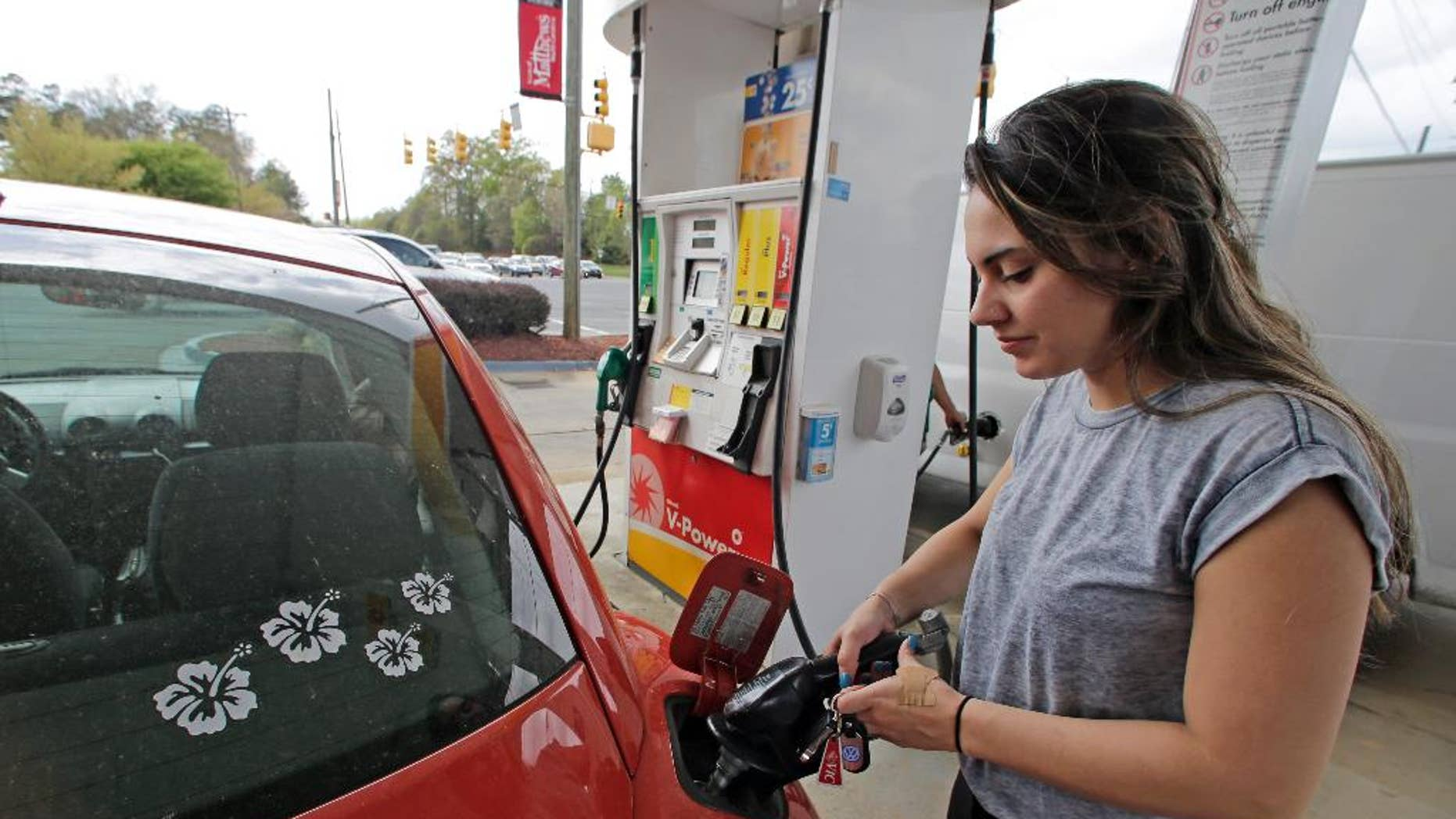 FILE - In this April 6, 2015 file photo, Lucy Perez, of Charlotte, N.C., pumps gas at a station in Matthews, N.C.  The University of Michigan issues its monthly index of consumer sentiment for April on Friday, May 1, 2015. (AP Photo/Chuck Burton, File)