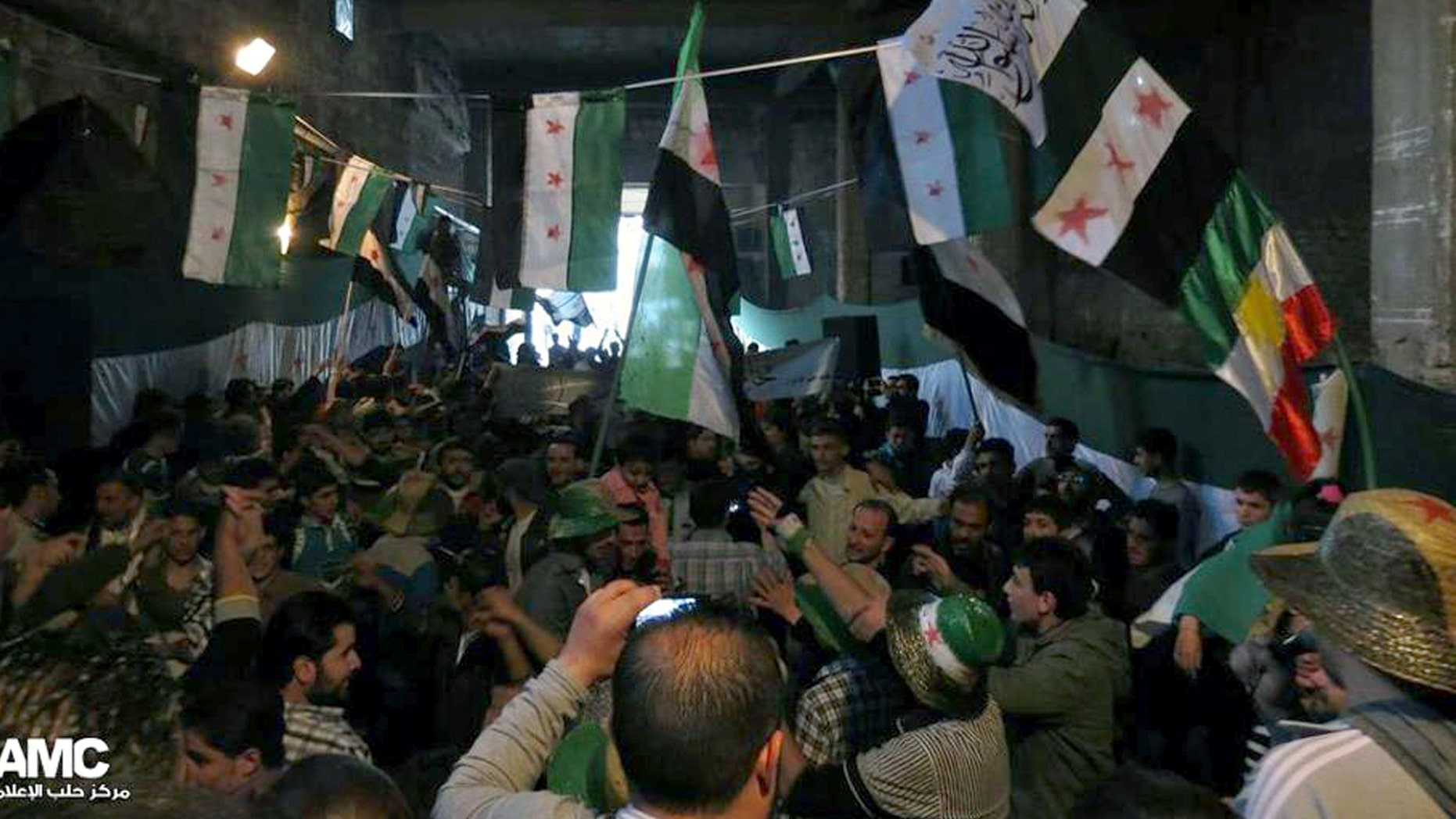 FILE: aPRIL 17, 2013: Anti-Syrian regime protesters holding Syrian revolution flags during a rally. The image provided by Aleppo Media Center AMC has been authenticated based on its contents and other reporting.