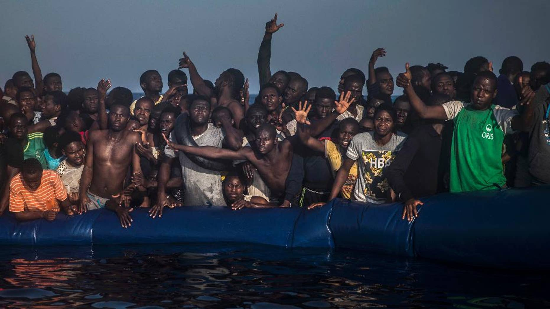 FILE- In this Saturday Sept. 10, 2016 file photo, African refugees and migrants react aboard a partially punctured rubber boat as they wait to be assisted , during a rescue operation on the Mediterranean Sea, about 13 miles North of Sabratha, Lybia. A popular Gambian wrestler has drowned trying to cross the Mediterranean Sea, the second high-profile athlete from the West African nation in the space of a few weeks to die trying to get to Europe on a boat of migrants. (AP Photo/Santi Palacios File)